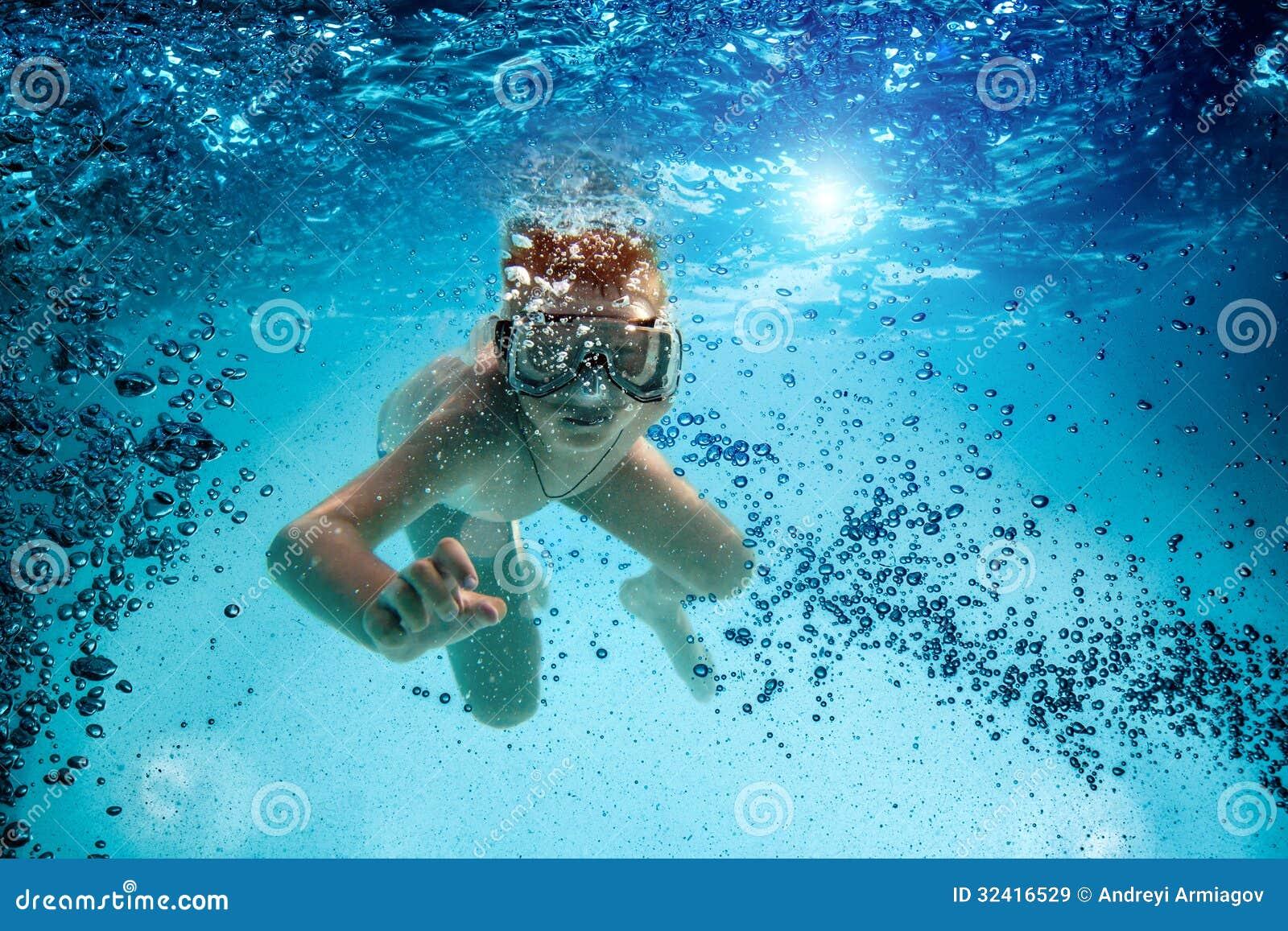 El adolescente en la máscara y el tubo respirador nadan bajo el agua.