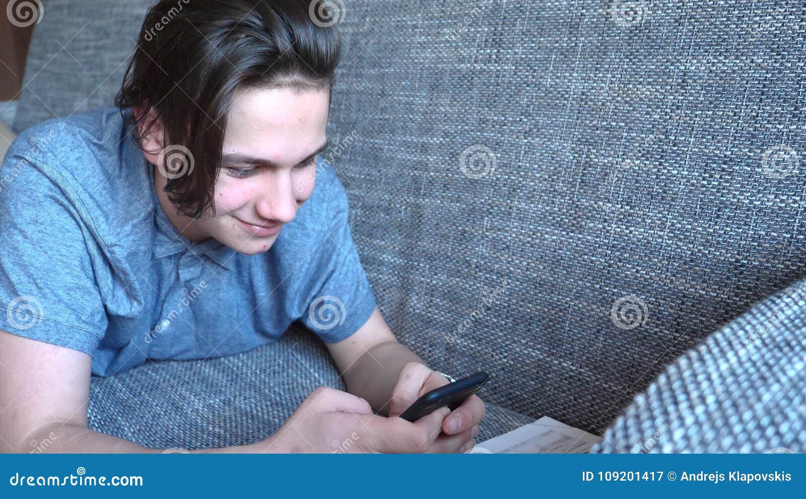 El adolescente hermoso del muchacho que habla en el teléfono se sienta en un sofá gris