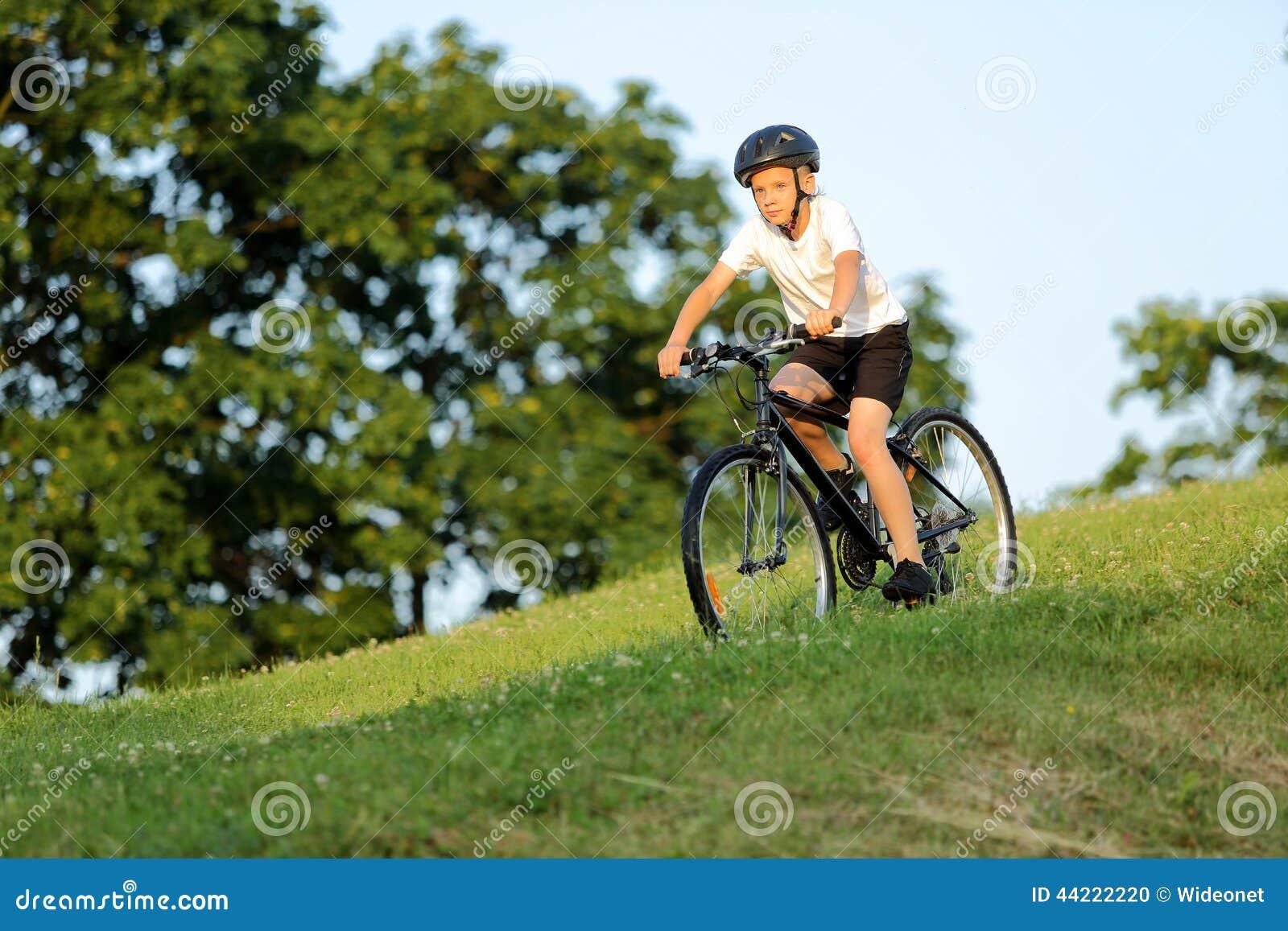 El adolescente monta una bici de la colina en parque de la ciudad