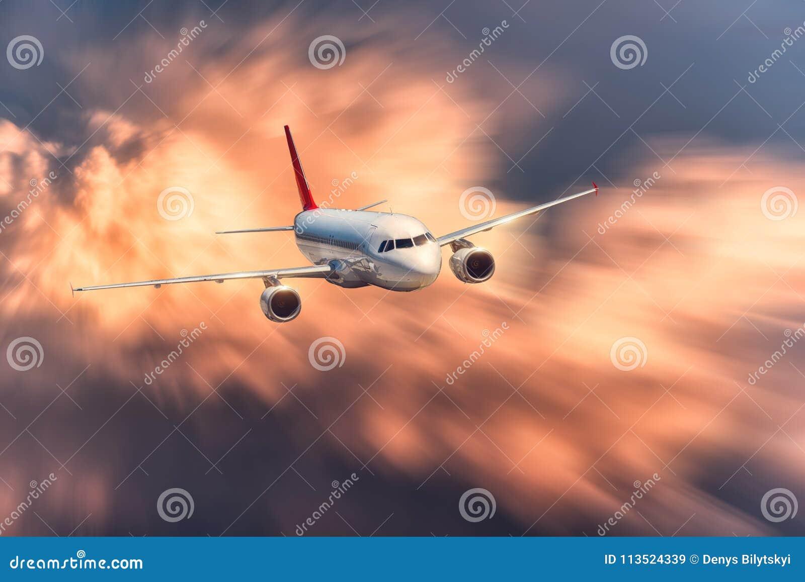 El aeroplano con efecto de la falta de definición de movimiento está volando en nubes anaranjadas grandes en la puesta del sol Ae
