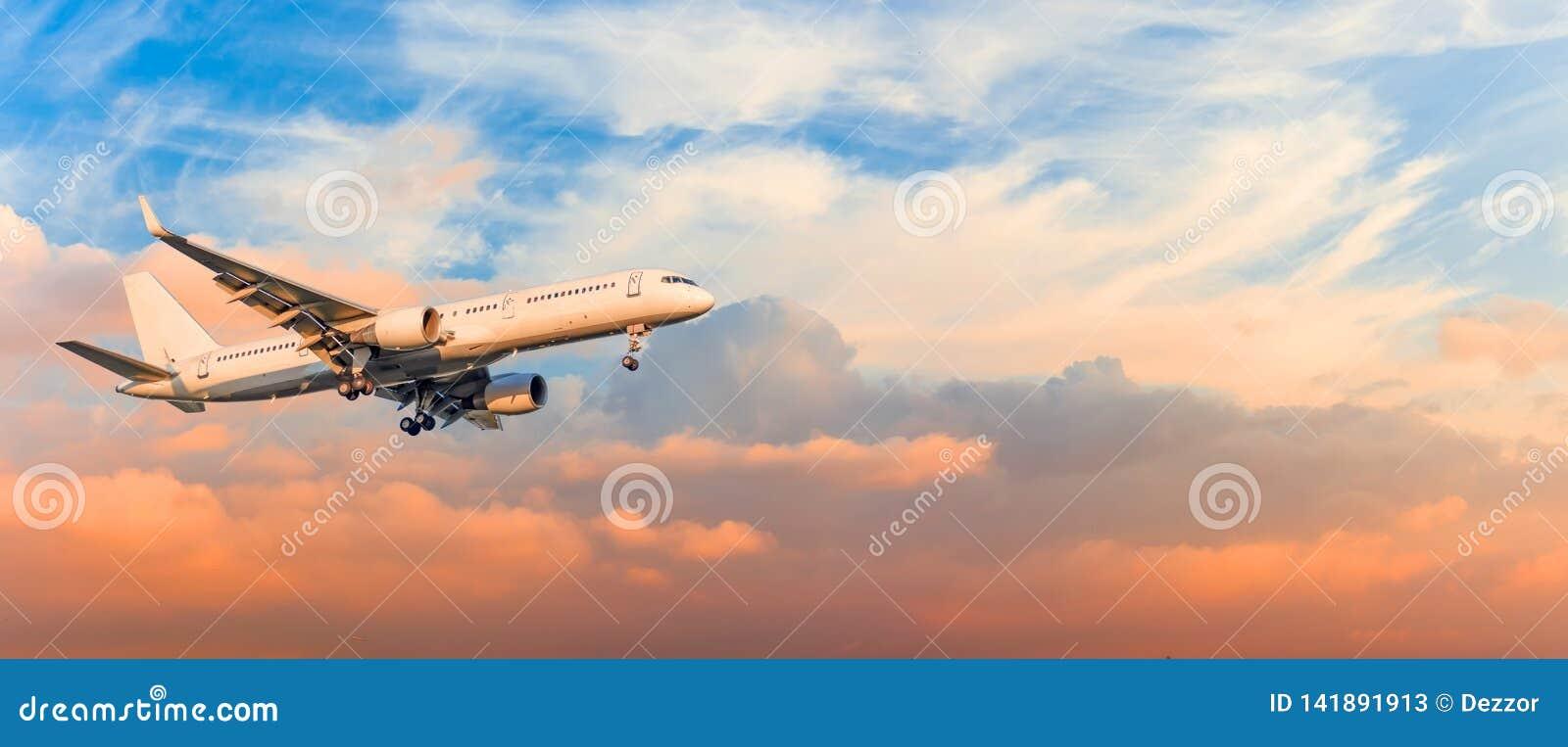 El aeroplano del pasajero es engranaje del acercamiento de aterrizaje lanzado, contra las nubes del cielo de la puesta del sol, p