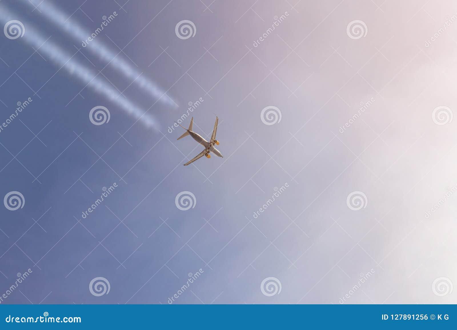 El aeroplano del pasajero que vuela arriba en el cielo claro que sale de blanco se arrastra Vuelo plano grande durante tiempo de