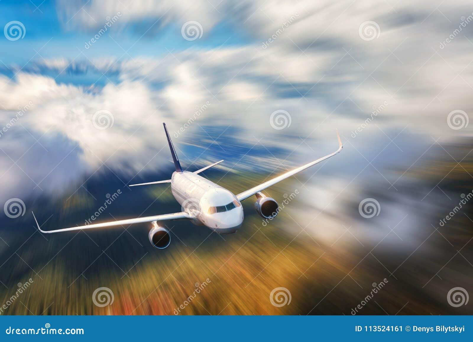 El aeroplano moderno con efecto de la falta de definición de movimiento está volando en nubes bajas en la puesta del sol Aeroplan