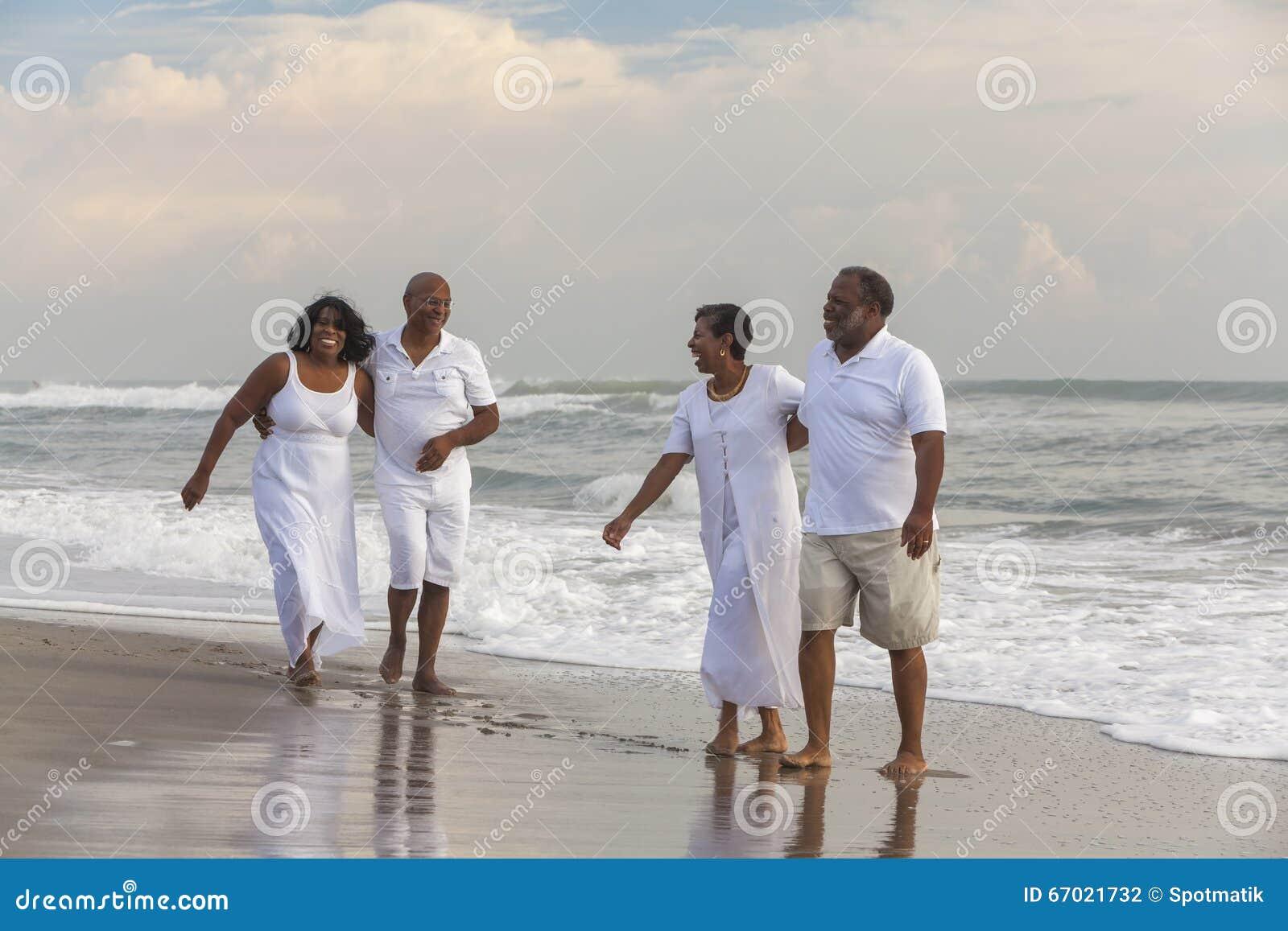 El afroamericano mayor feliz junta a mujeres de los hombres en la playa