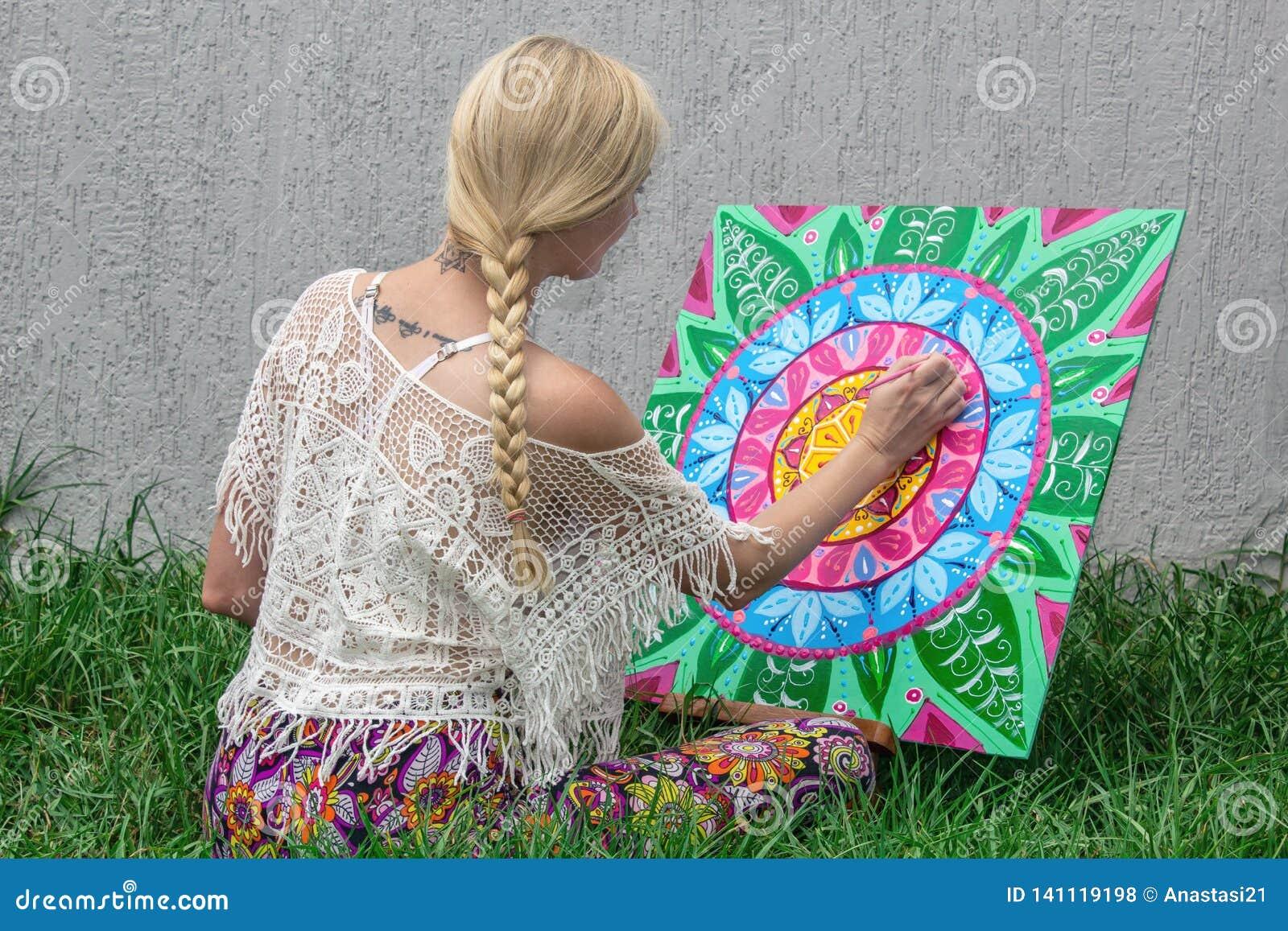 El aire libre de pintura, una mujer joven rubia dibuja una mandala en la naturaleza que se sienta en la hierba