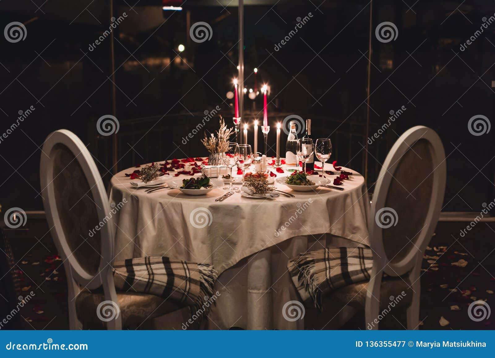 El ajuste romántico de la tabla con el vino, flores hermosas en caja, vidrios vacíos, subió los pétalos y las velas