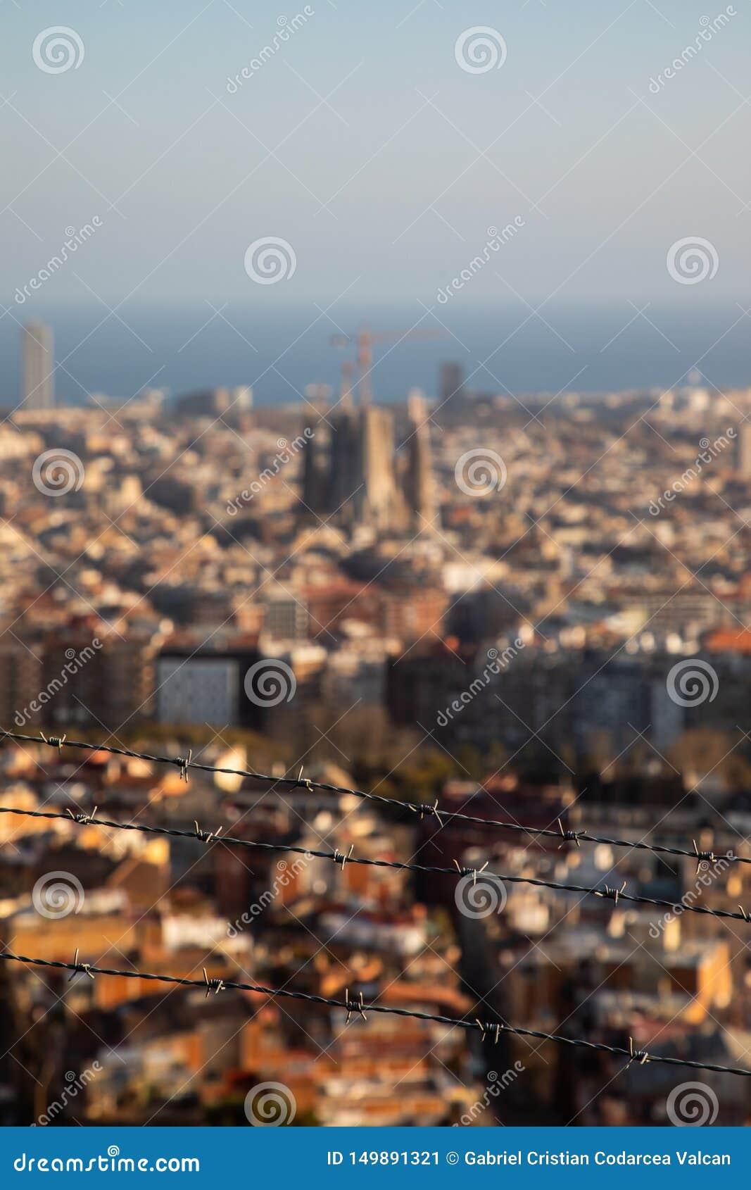 El alambre de púas enfocado con la ciudad de Barcelona empañó en fondo