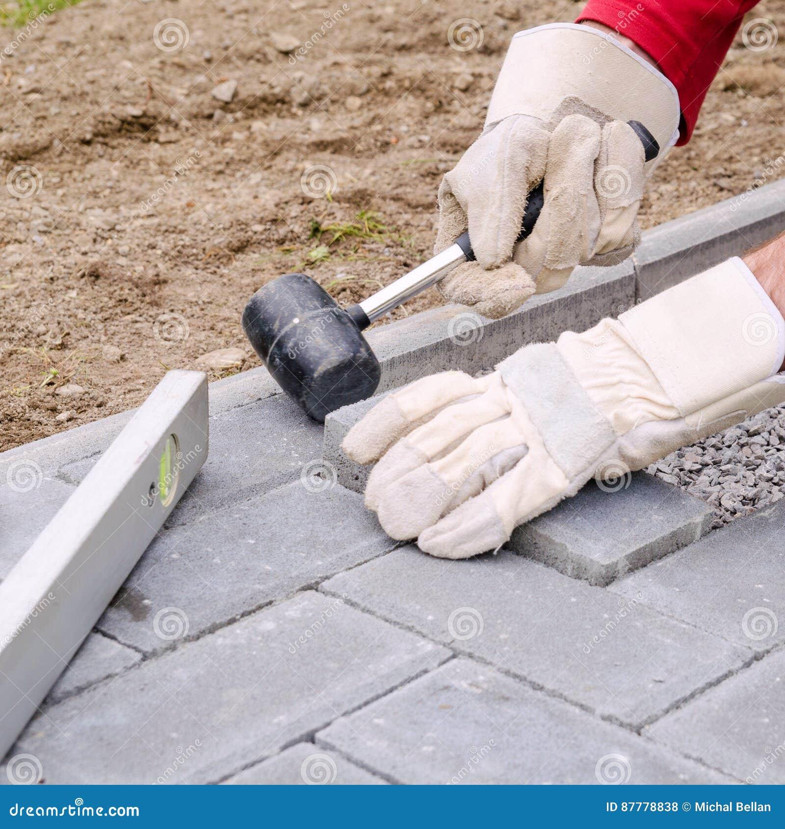 El albañil pone los bloques concretos de la piedra de pavimentación para acumular un patio de la pavimentación, usando el martill