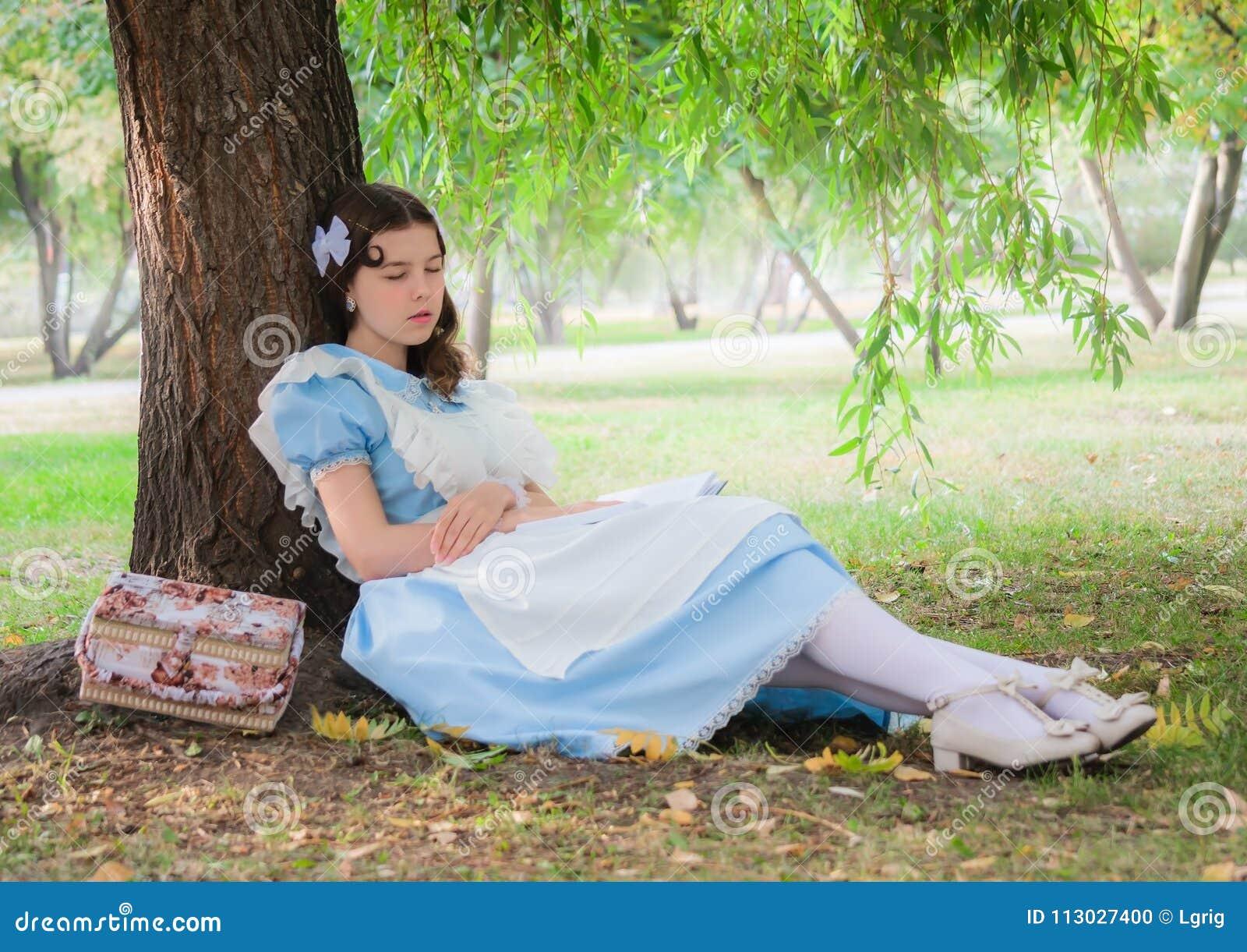El alumno de la muchacha cayó sueño debajo de un árbol con un libro