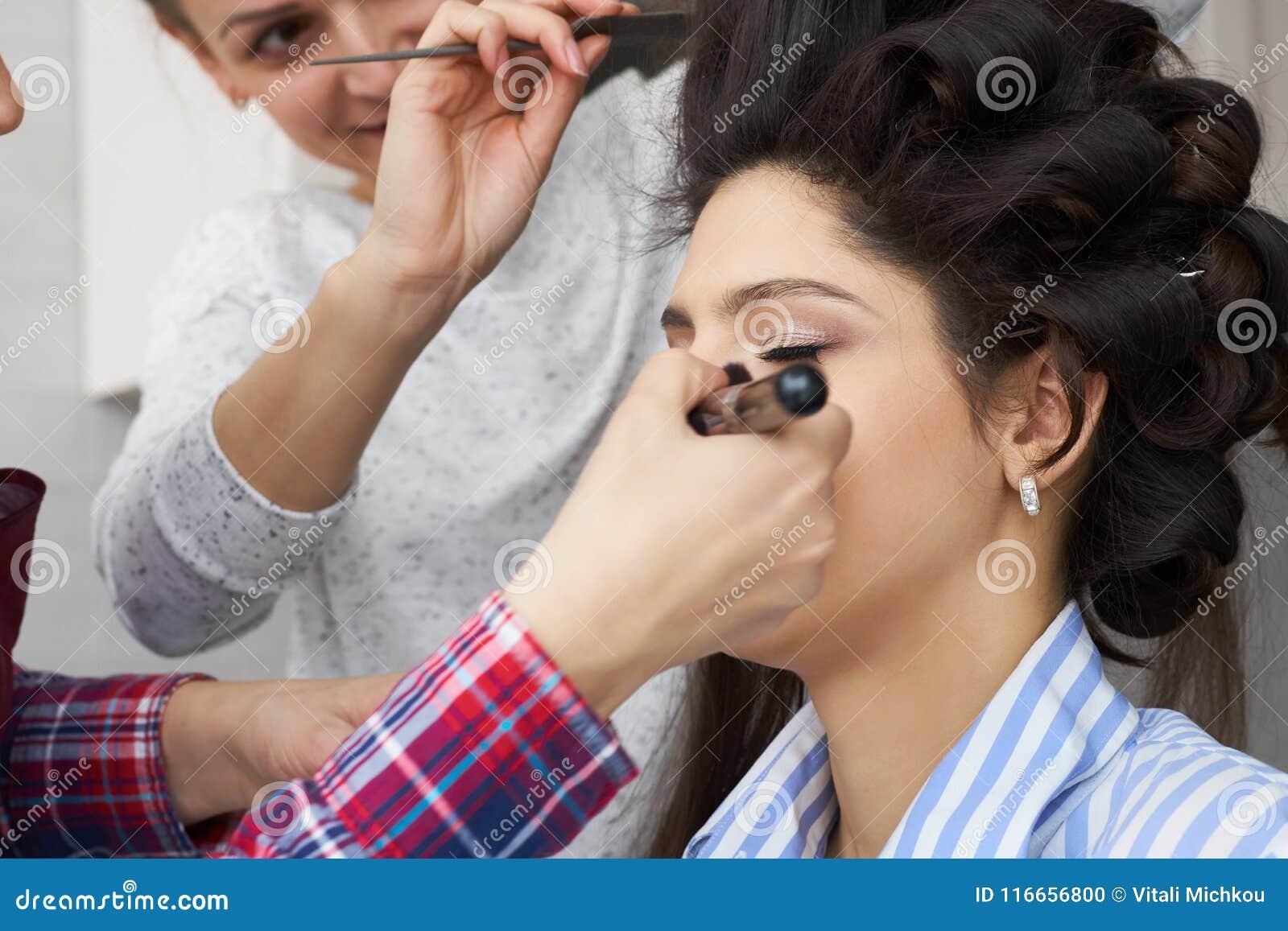 El amo inflige el polvo del cepillo en la cara de la muchacha, termina el maquillaje del día en un salón de belleza