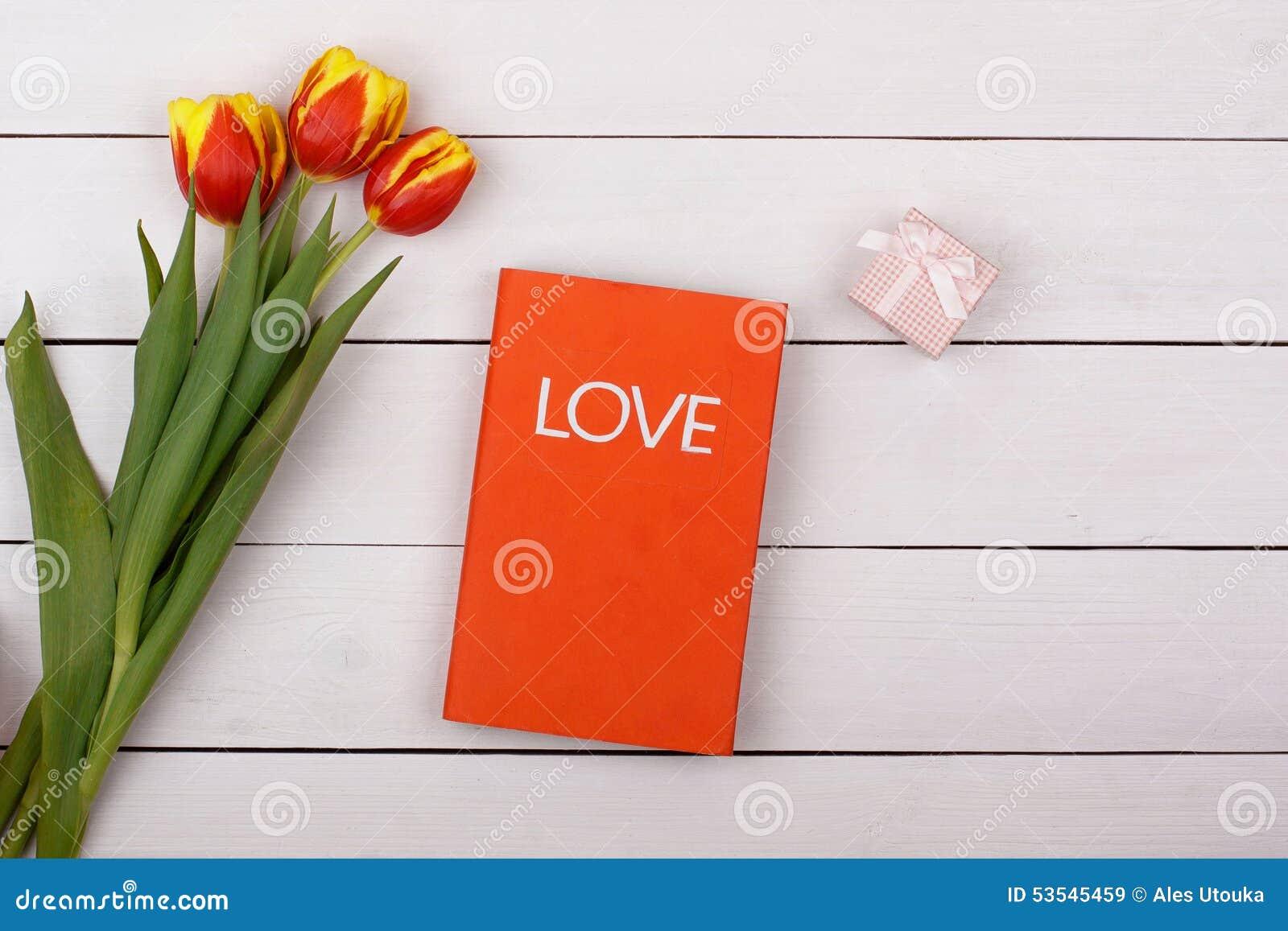 El amor rojo del libro miente en una tabla blanca tulipanes y regalo de las flores