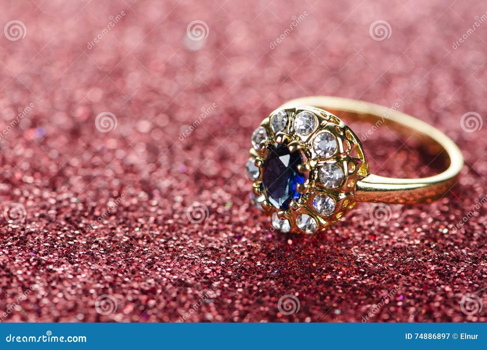 El anillo de la joyería contra fondo brillante