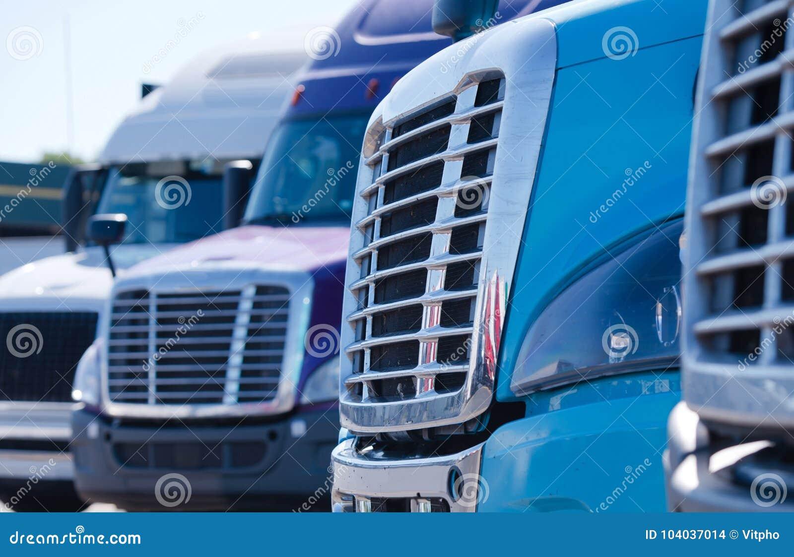 El aparejo grande semi acarrea parrillas de los tractores en fila en la parada de camiones