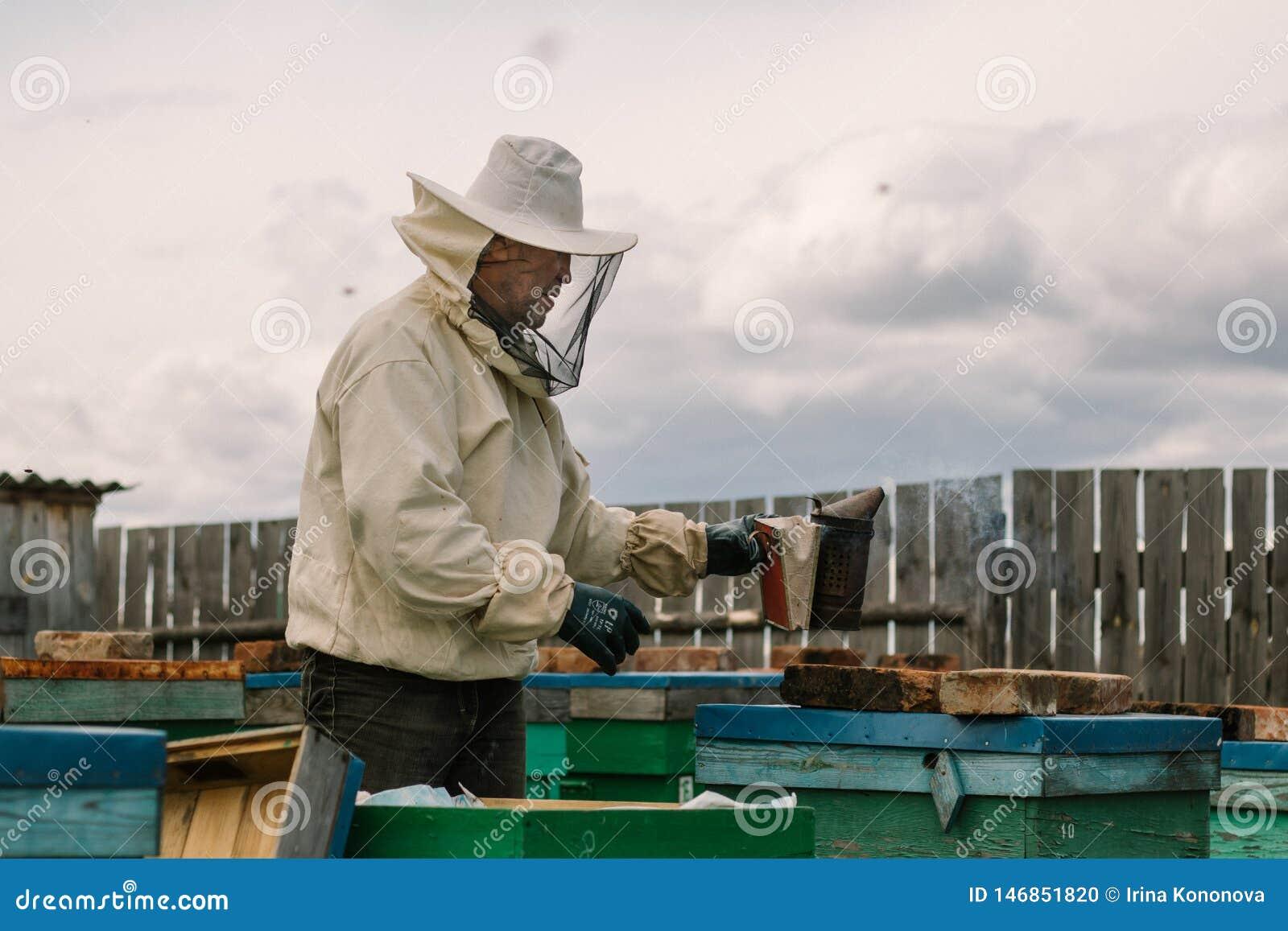 El apicultor en un traje protector fumiga colmenas