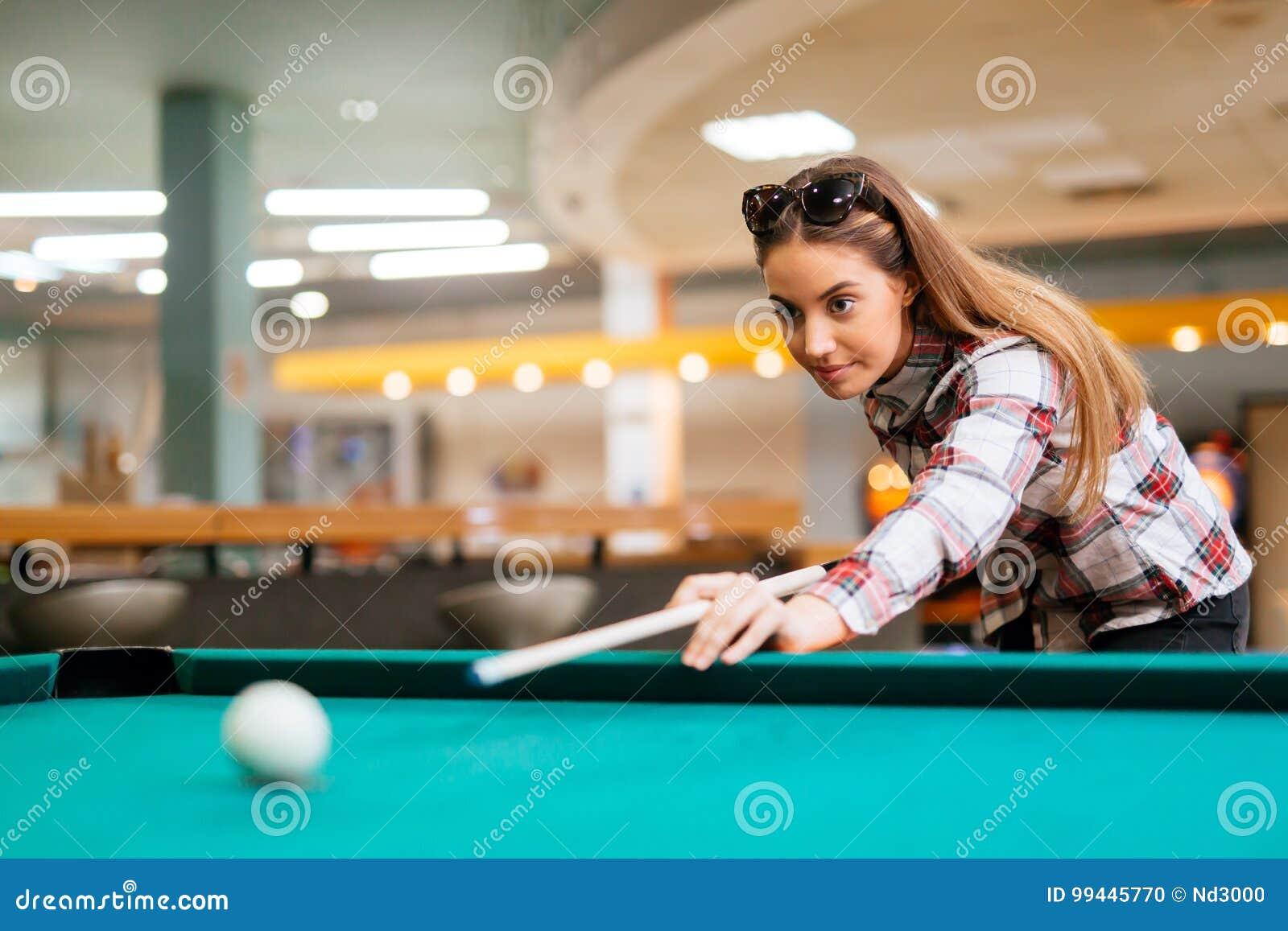 El apuntar moreno mientras que juega el billar