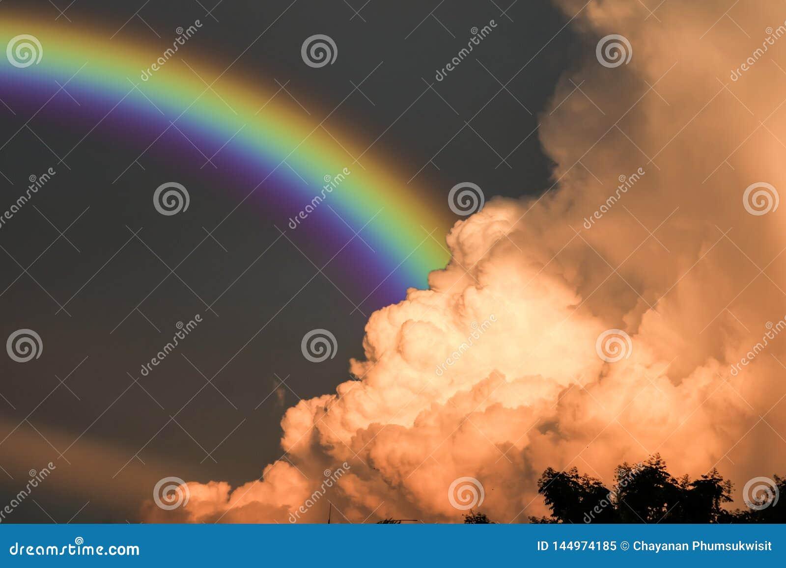El arco iris aparece en el cielo después de la lluvia y de la parte posterior en la nube de la puesta del sol