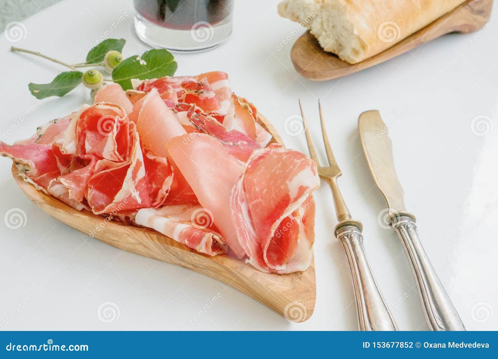 El aroma del jamón y de especias, cortado fino en una tabla blanca con los cubiertos y el vino tinto antiguos del pan
