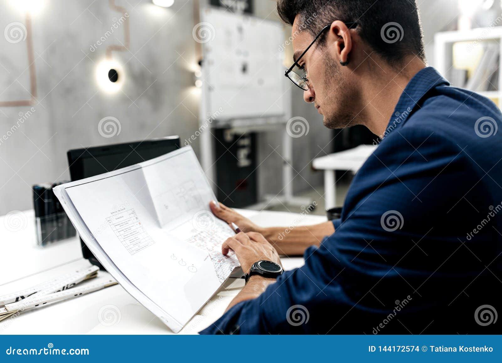 El arquitecto oscuro-cabelludo elegante en vidrios y en una chaqueta azul está trabajando con los documentos en el escritorio en