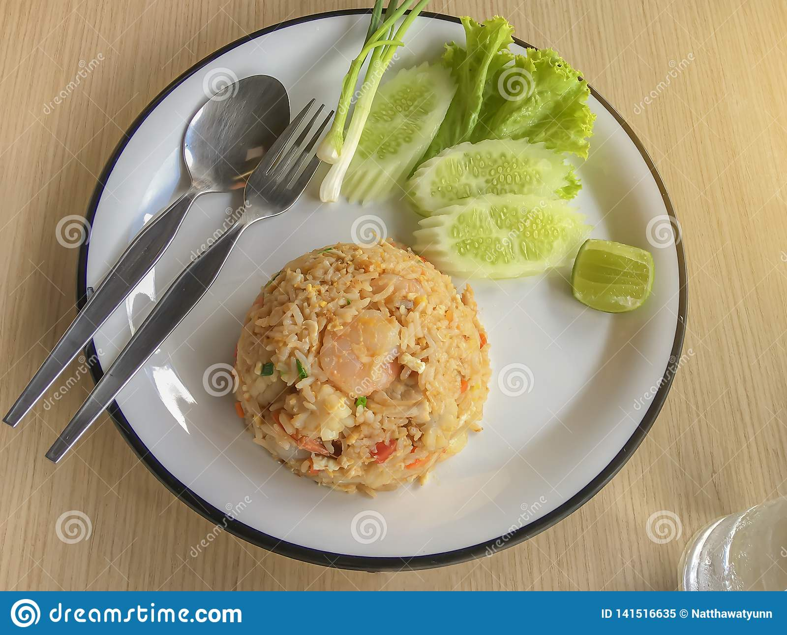 El arroz frito con el camarón en tailandés adorna el plato con la cebolla verde, el pepino, la lechuga, los chiles y el limón