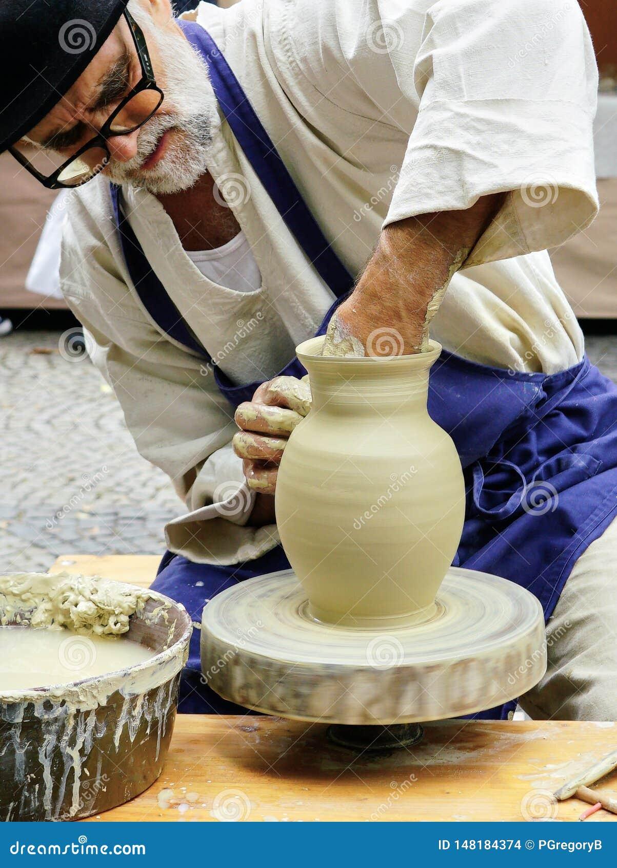 El artesano mayor hace girar la cerámica en su rueda en la feria del arte en Bratislava