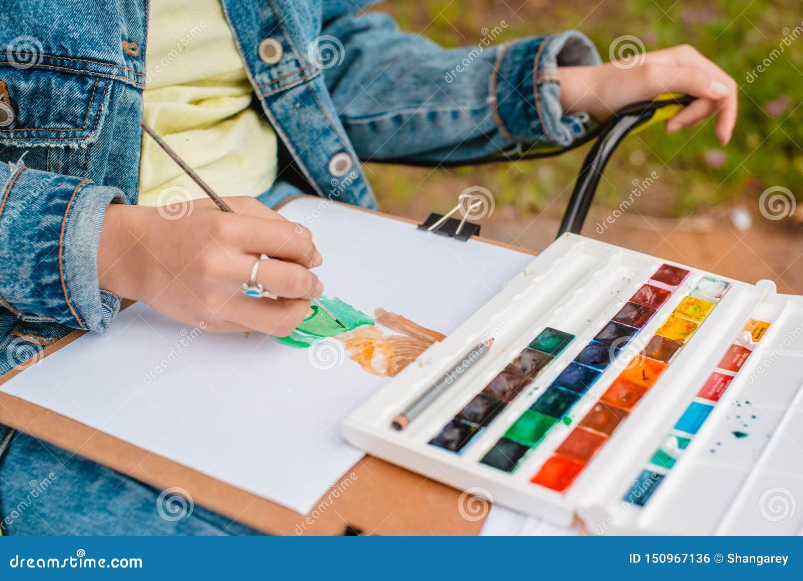 El artista creativo pinta una imagen colorida Primer de manos y del cepillo en curso de pintura al aire libre