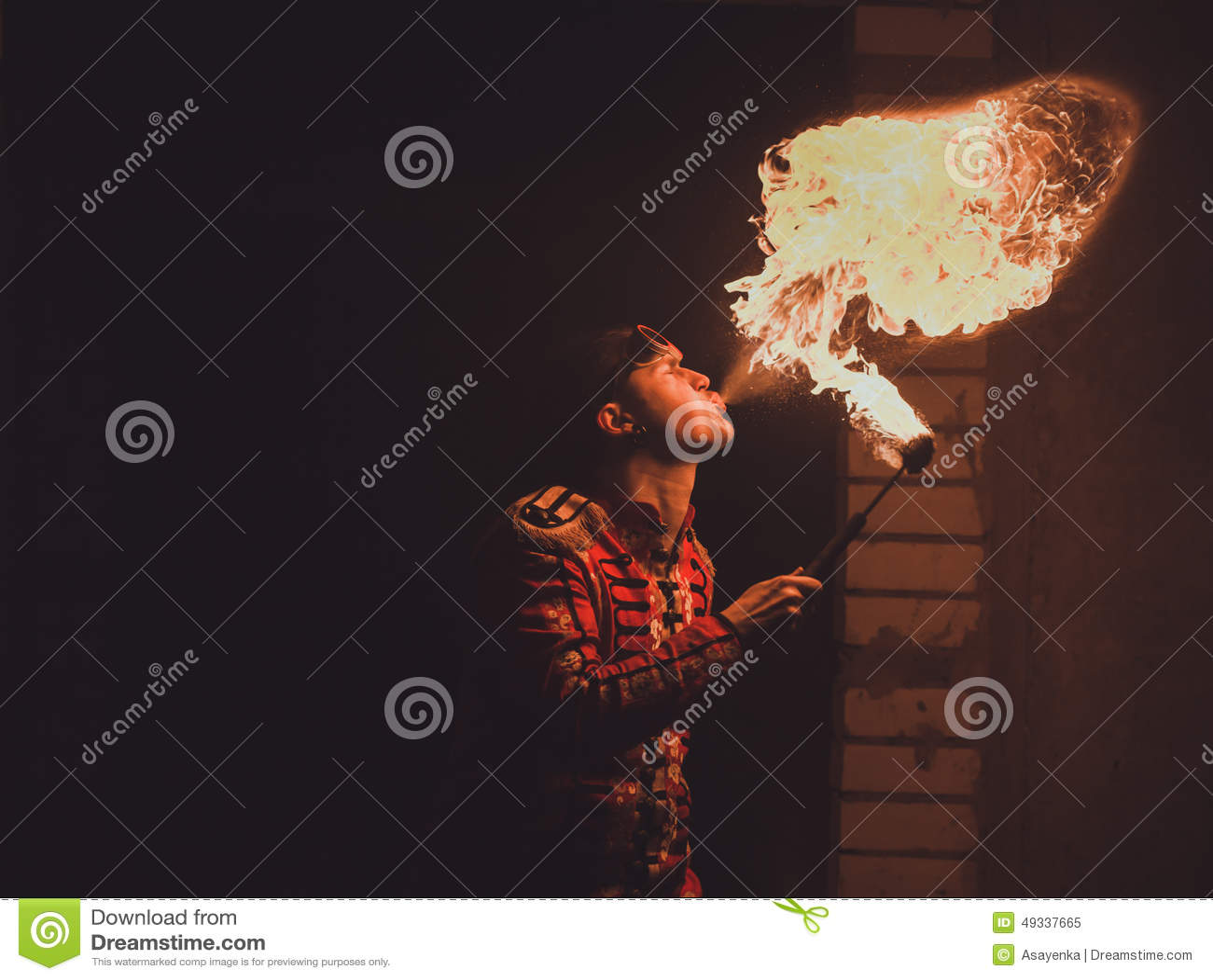 El artista de la demostración del fuego respira el fuego en la oscuridad