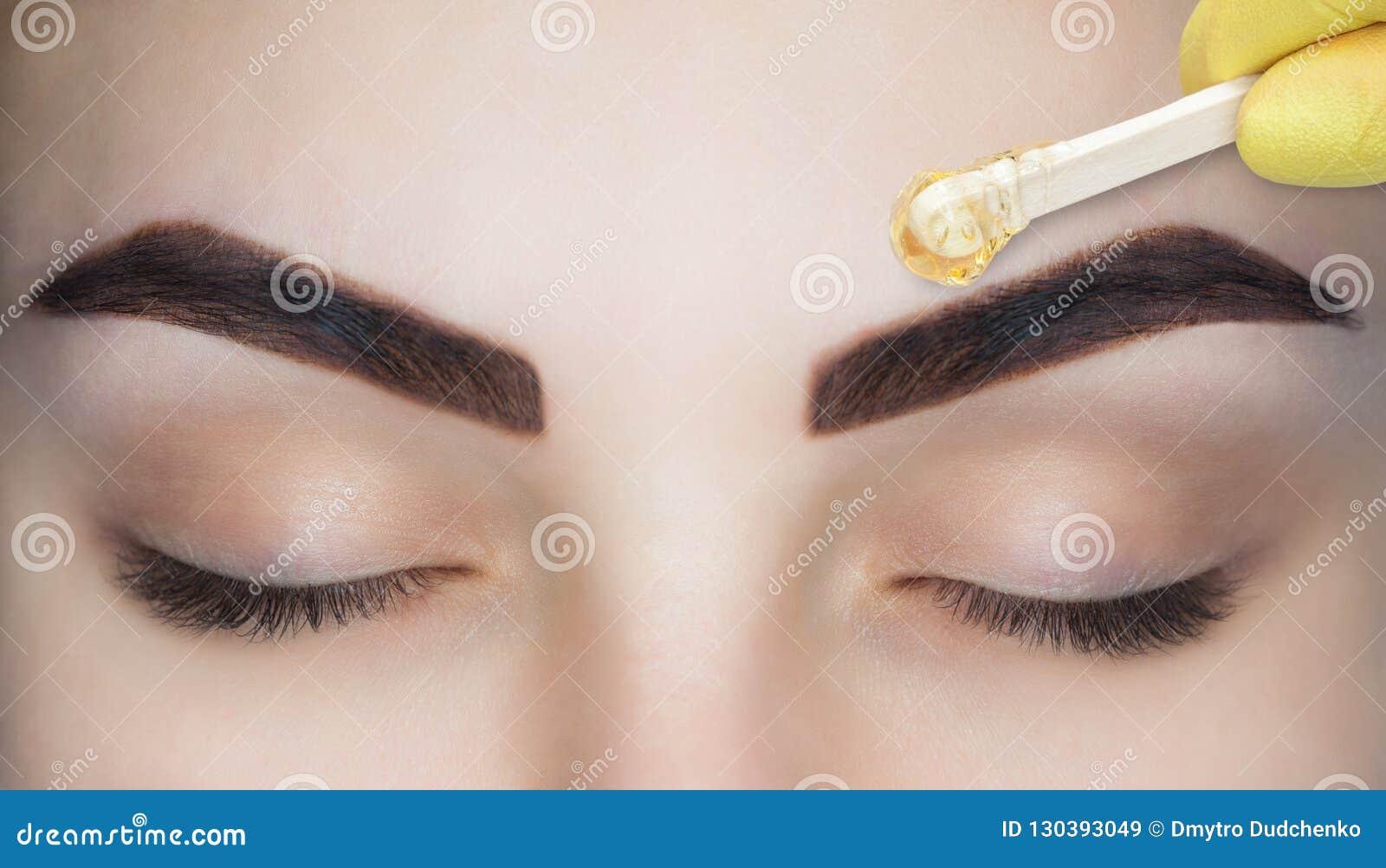 El artista de maquillaje despluma sus cejas, antes del procedimiento del maquillaje permanente