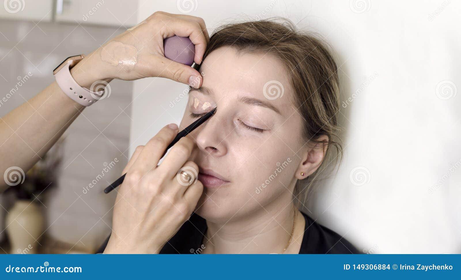 El artista de maquillaje hace el maquillaje para la muchacha