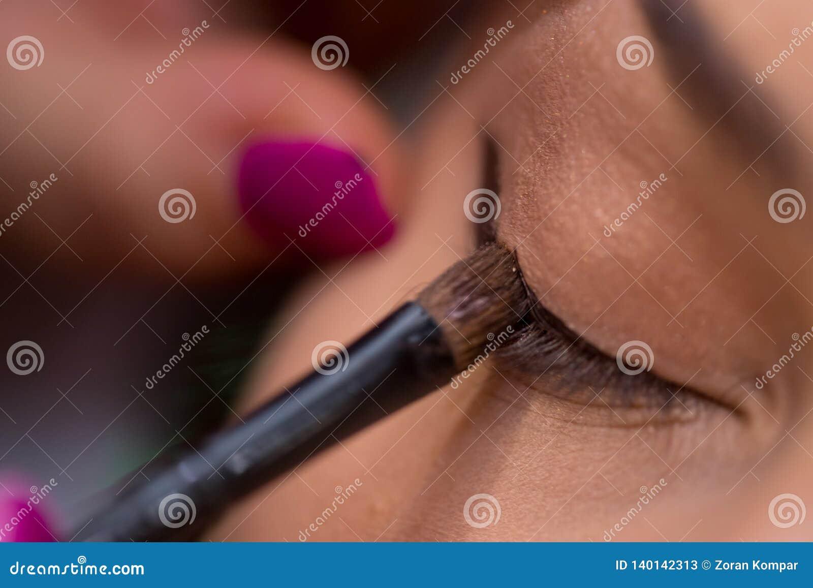 El artista de maquillaje pone el trazador de líneas del ojo en el ojo de la mujer en el salón