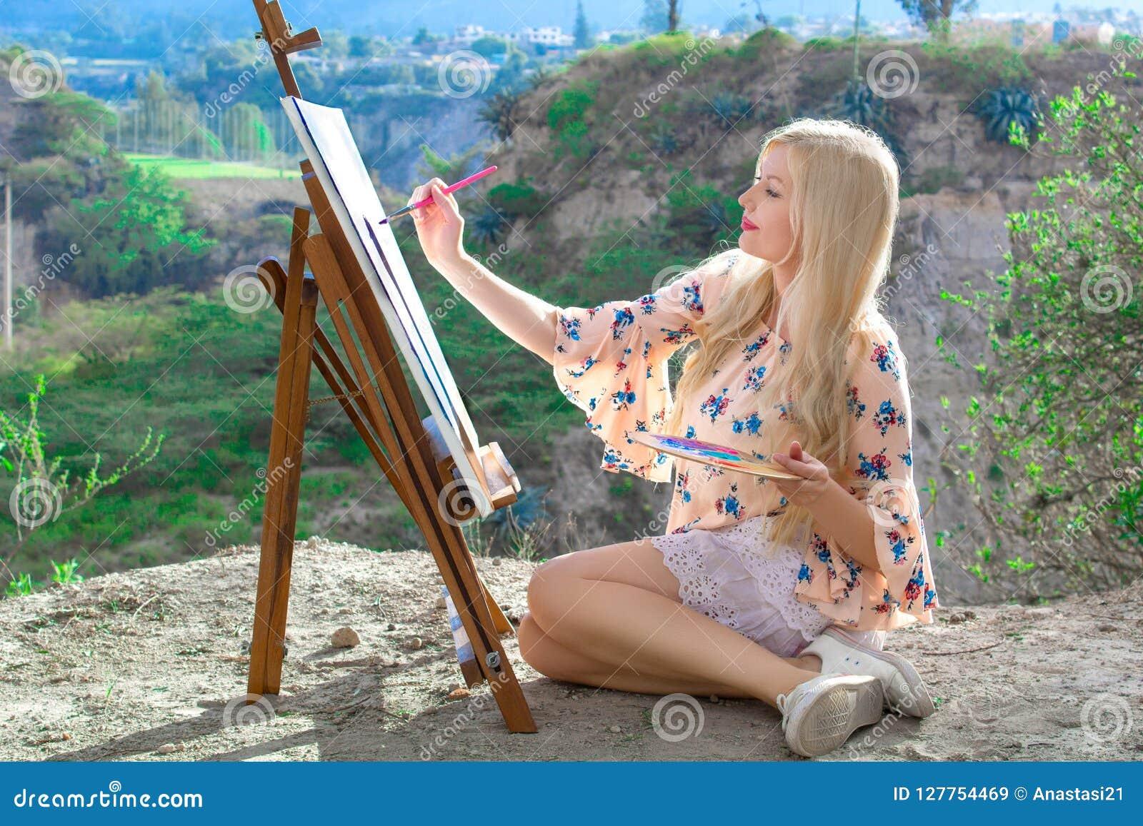 El artista hermoso de la mujer joven pinta un paisaje en naturaleza Dibujo en el caballete con las pinturas coloridas en el aire