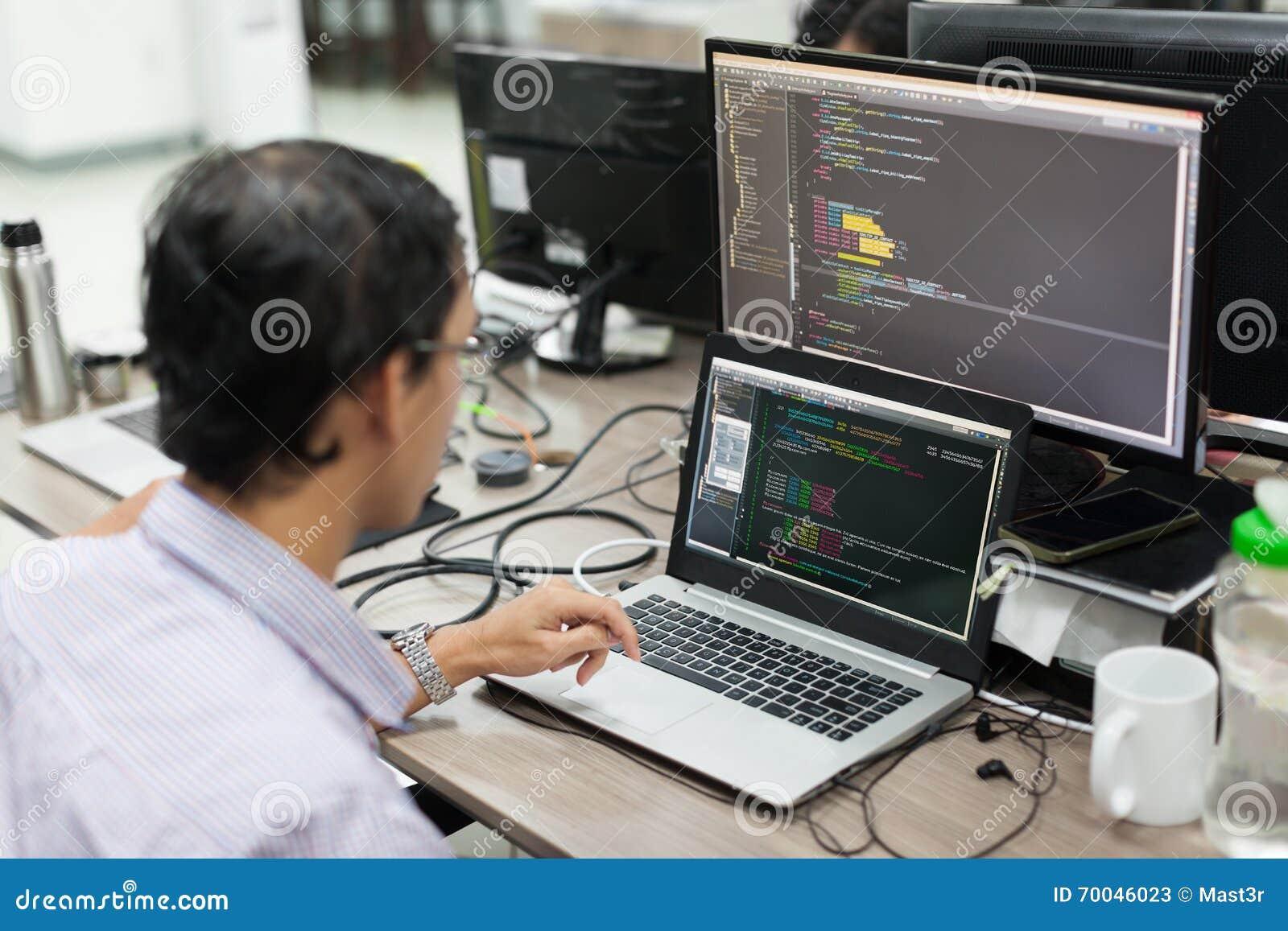 El asiático externaliza el desarrollador de software que mira la pantalla que se sienta el escritorio