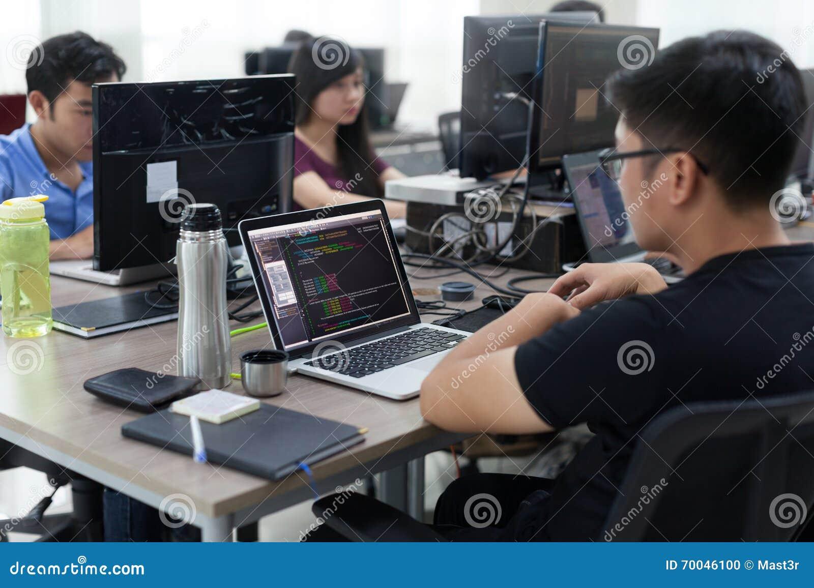 El asiático externaliza el ordenador portátil de Team Sitting At Desk Working del desarrollador