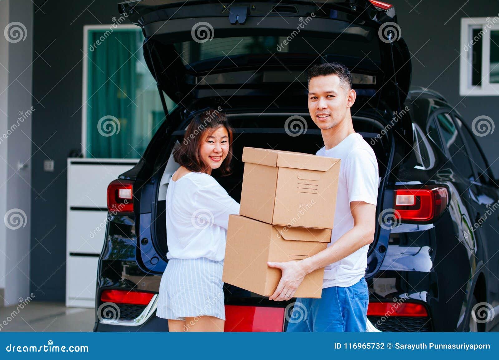 El asiático feliz maduro casó las cajas de cartón de la pareja que llevaban del tronco de coche en el nuevo hogar