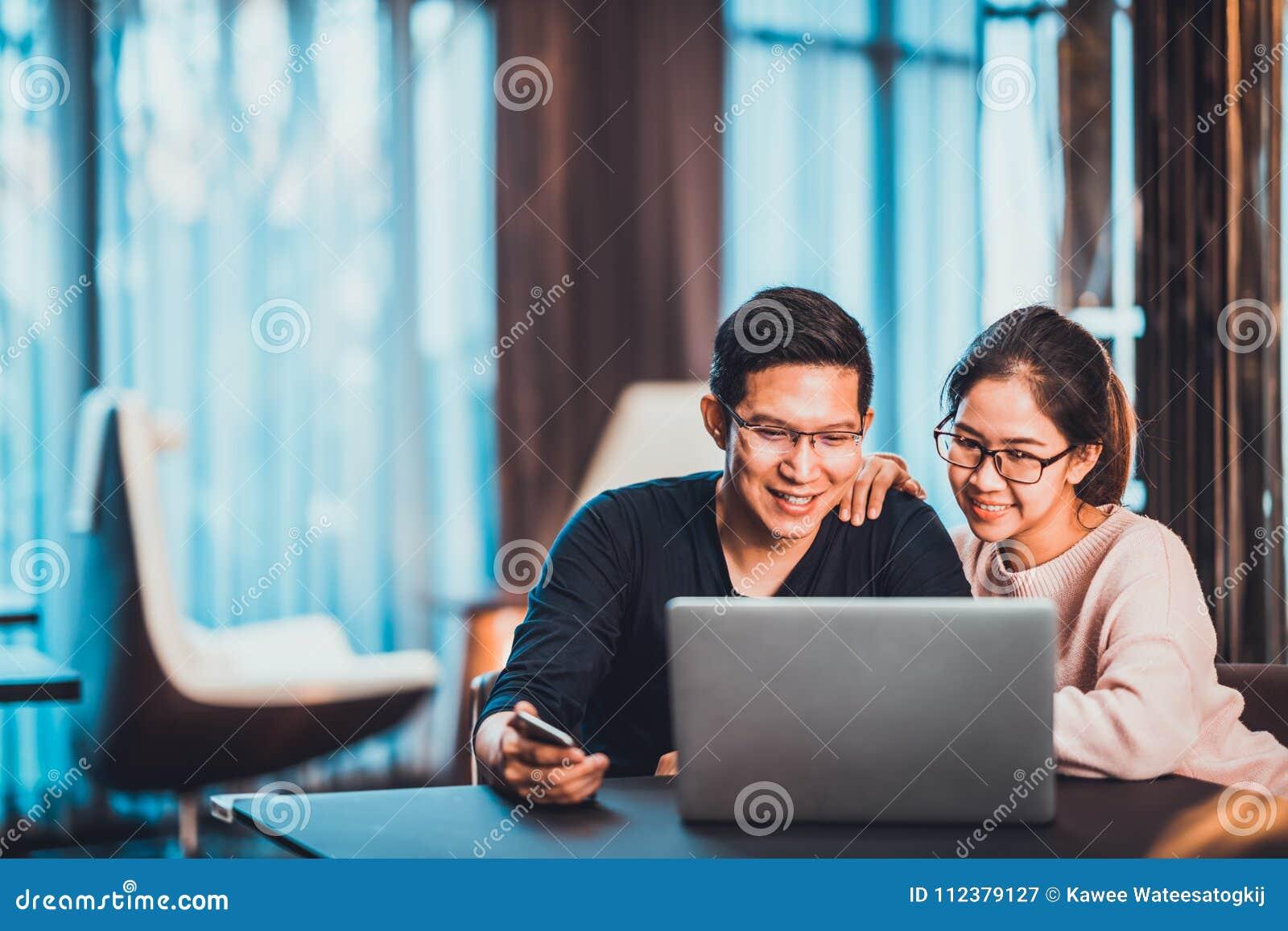 El asiático joven casó a la pareja que trabajaba junto usando el ordenador portátil en casa o la oficina moderna con el espacio d