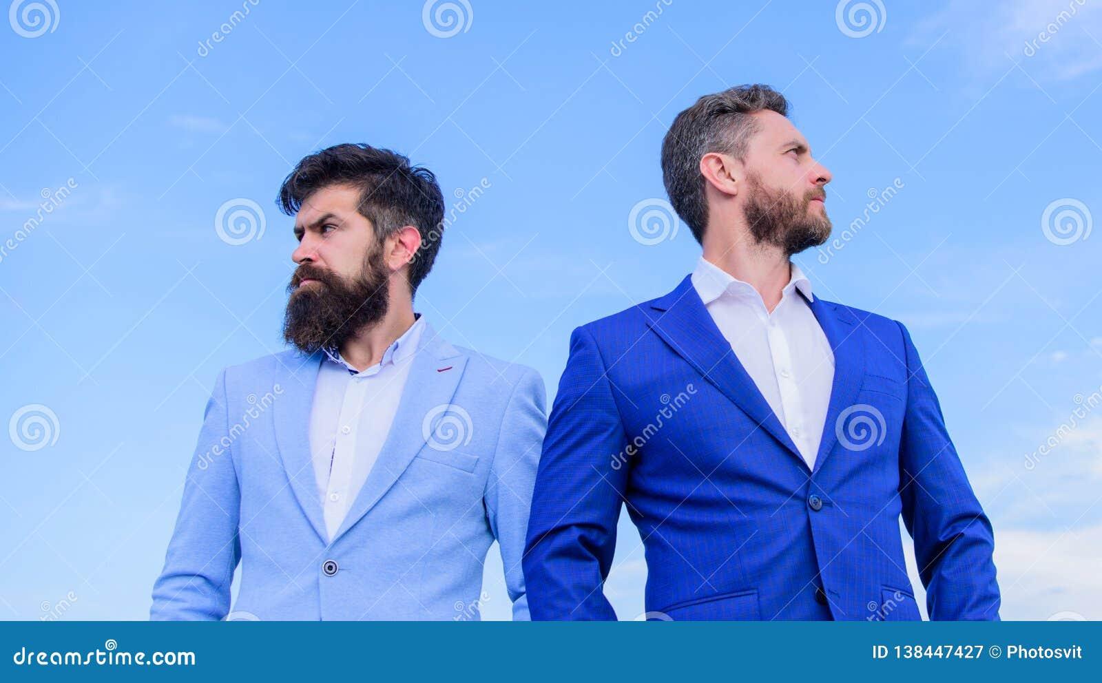 El aspecto preparado bien mejora al empresario de la reputación del negocio Hombres de negocios barbudos que presentan con confia