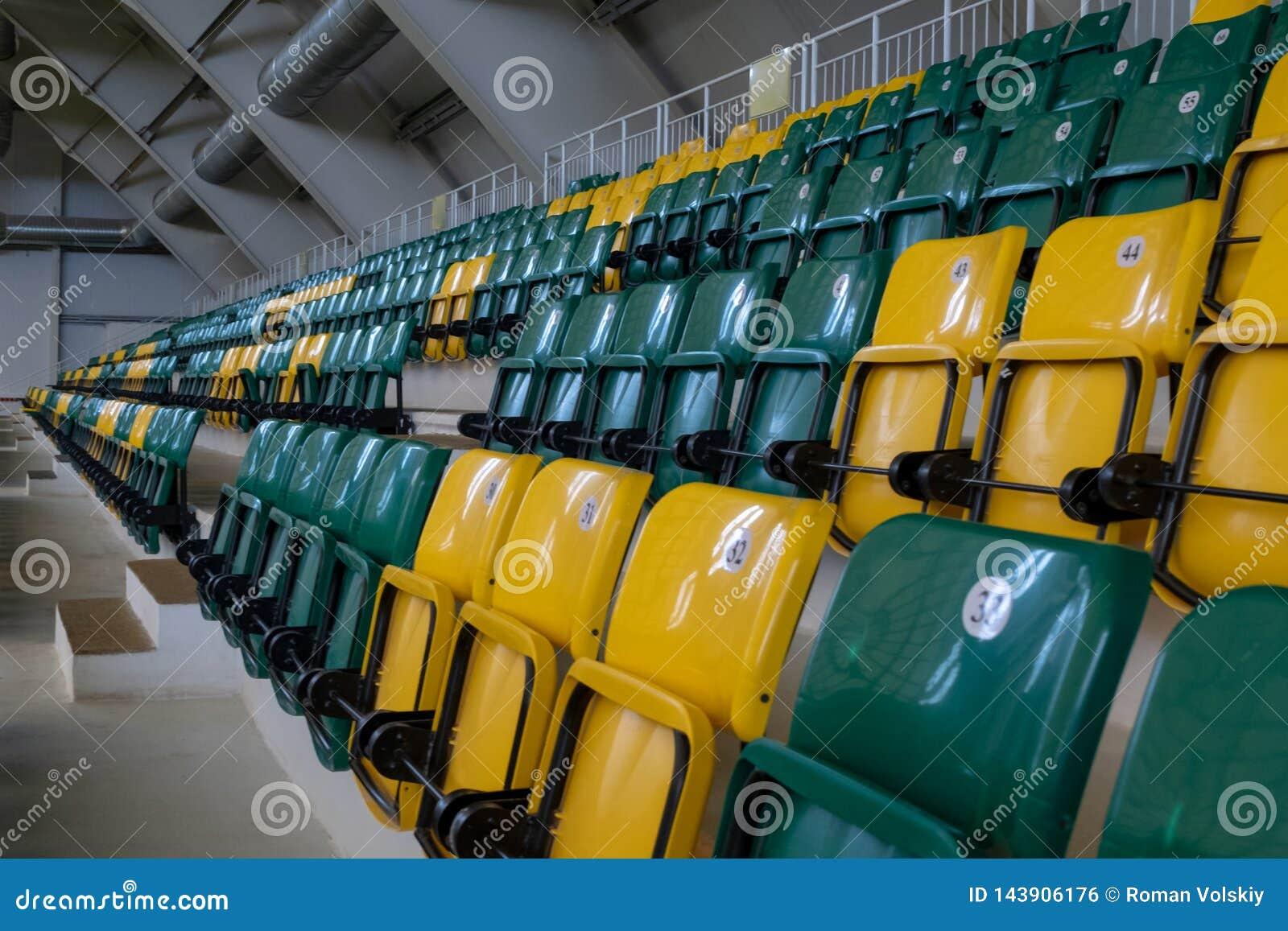 El auditorio en el complejo de los deportes con los asientos pl?sticos verdes y amarillos Los lugares para los espectadores del l