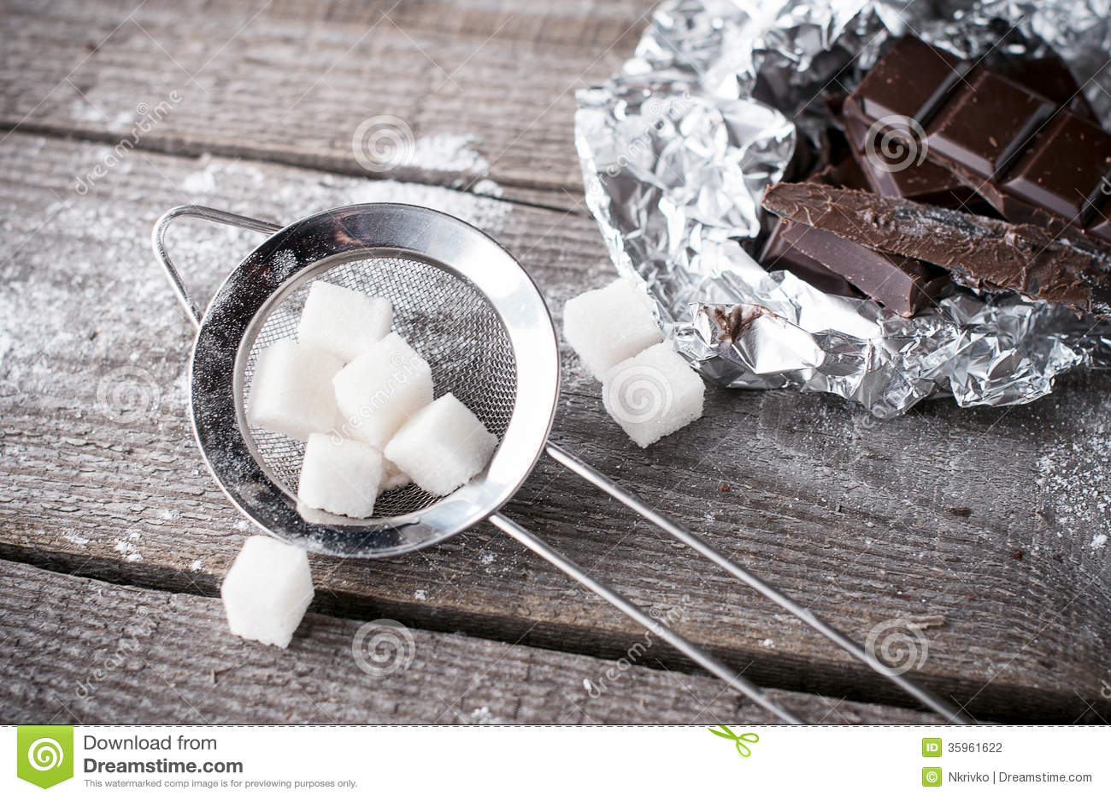 El azúcar de terrón en un tamiz y un chocolate oscuro negro del metal junta las piezas de o
