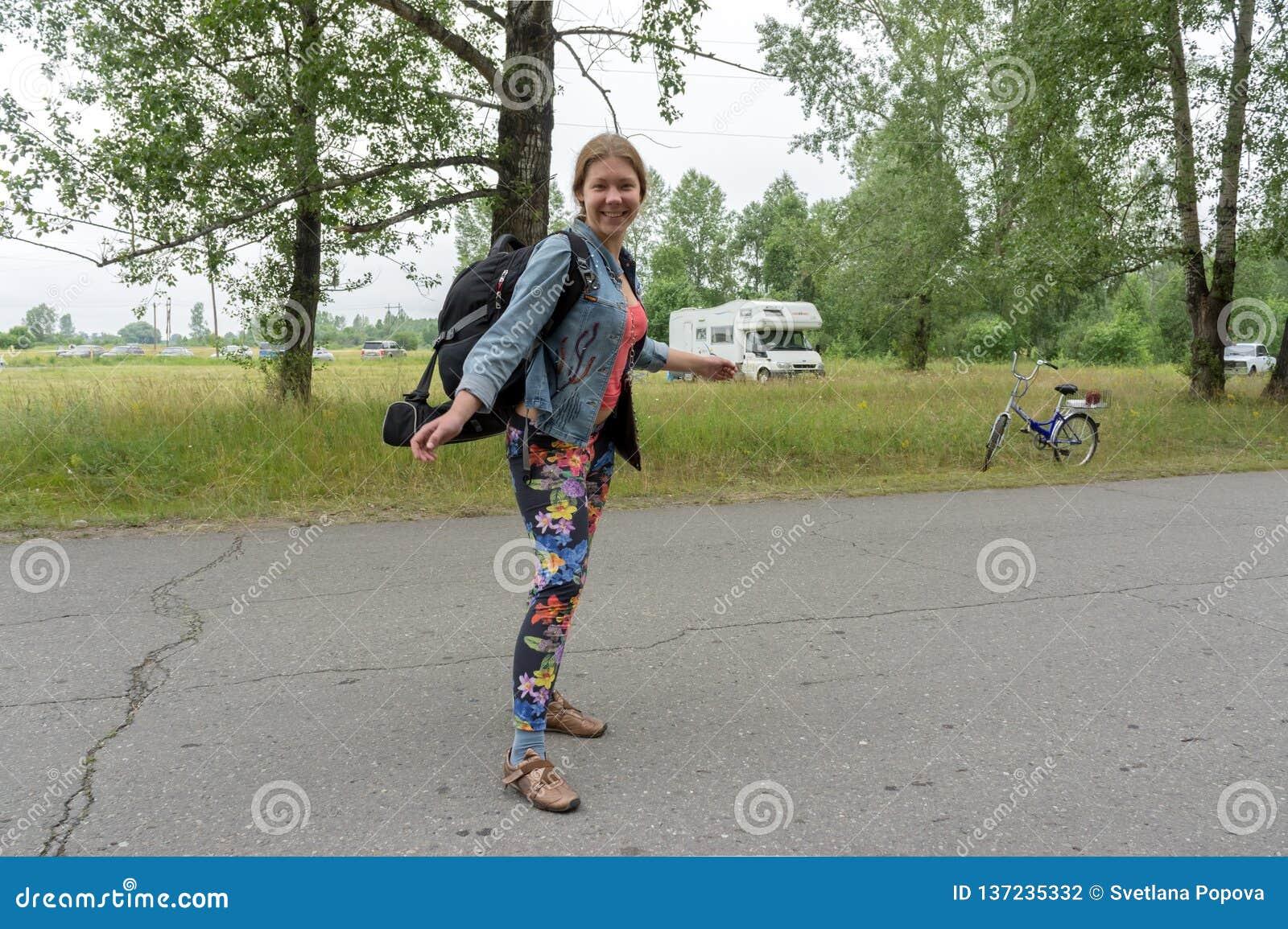 El backpacker feliz de la muchacha se coloca con una mochila en el camino, contra la perspectiva de árboles en un día de verano