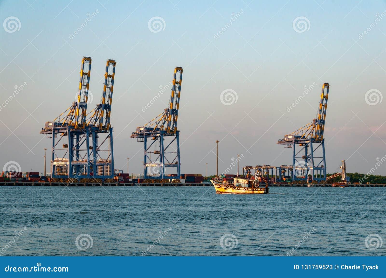 El barco de pesca pone hacia fuera al mar del puerto de Cochi, con industria pesada en el fondo