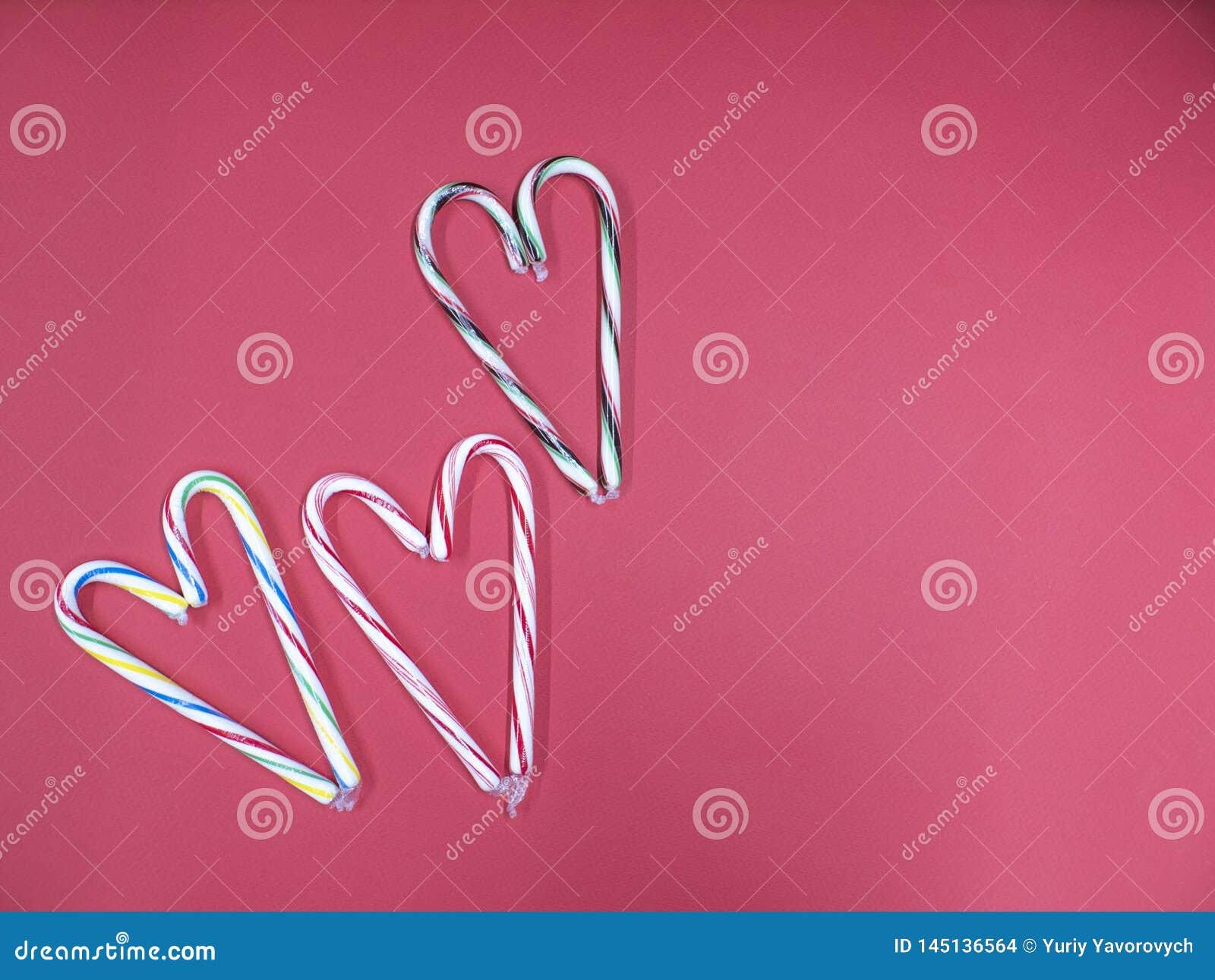 El bastón del caramelo tres dobló en la forma de un corazón en un fondo rosado