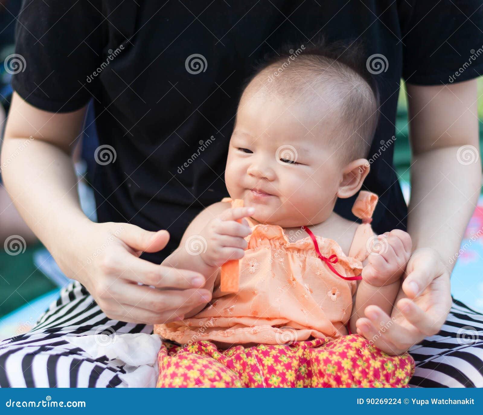 El bebé asiático lindo goza el probar de la zanahoria