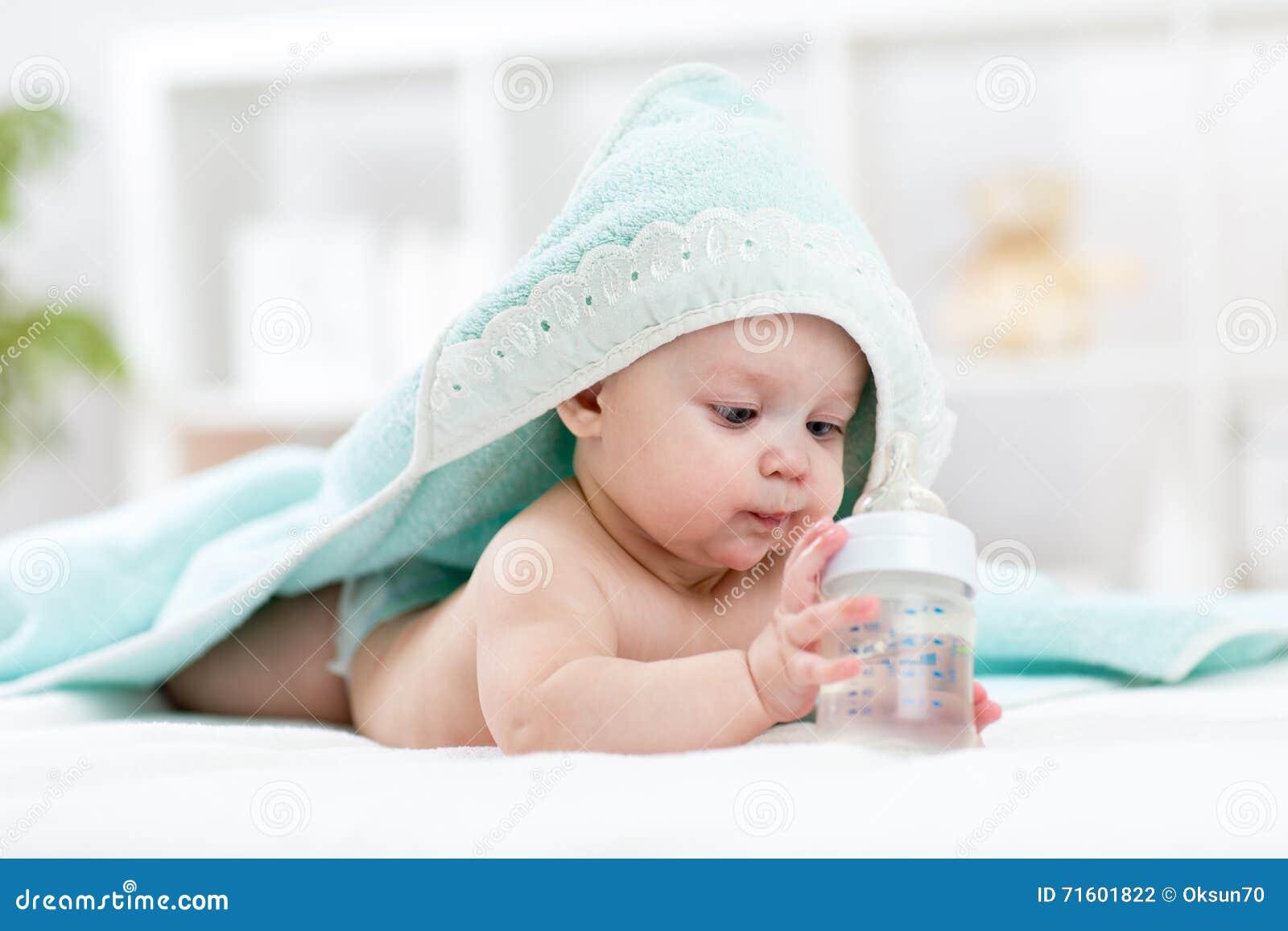 El bebé bebe el agua de la toalla cubierta botella después de baño