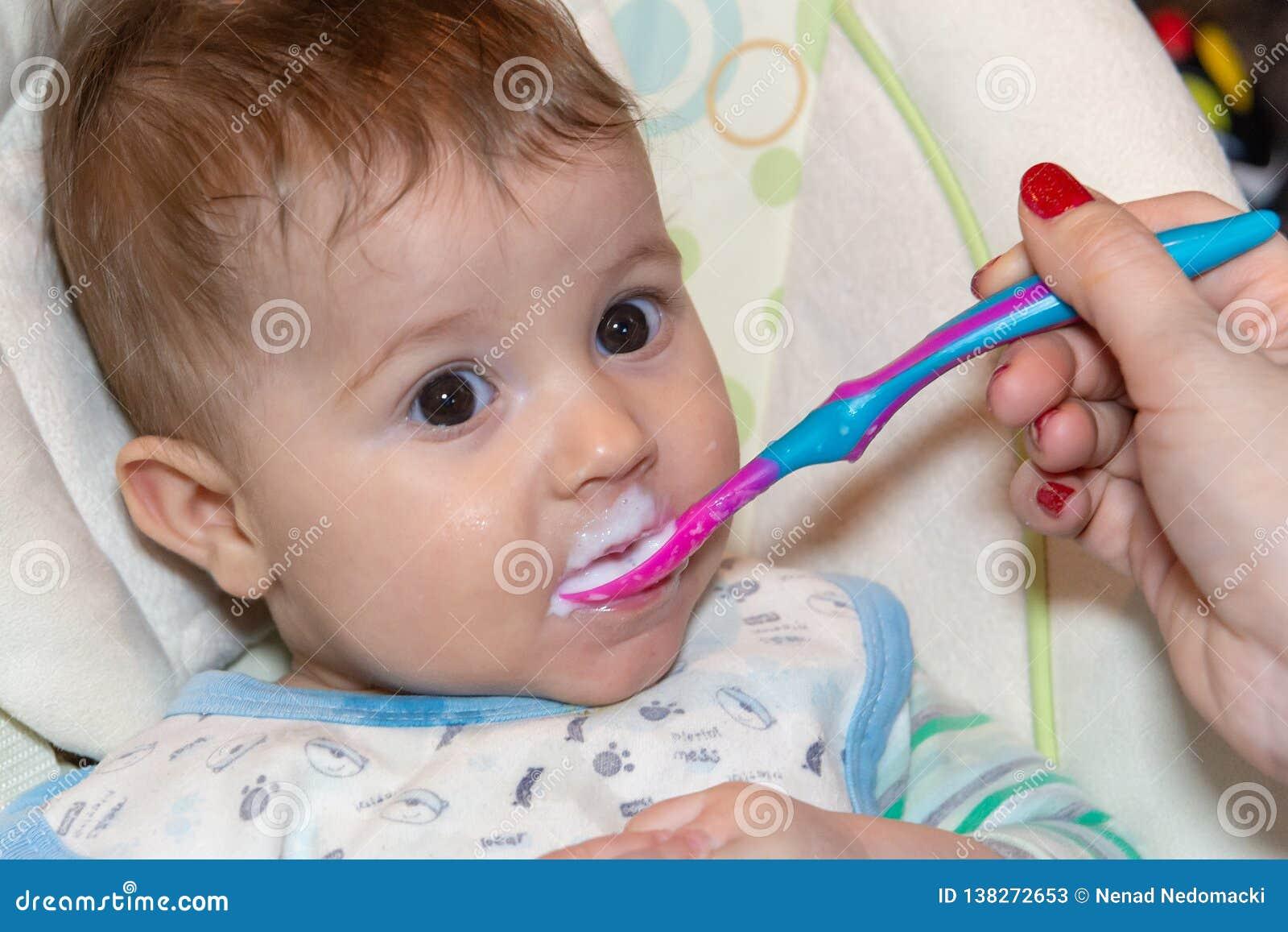 El bebé come la comida sólida por primera vez