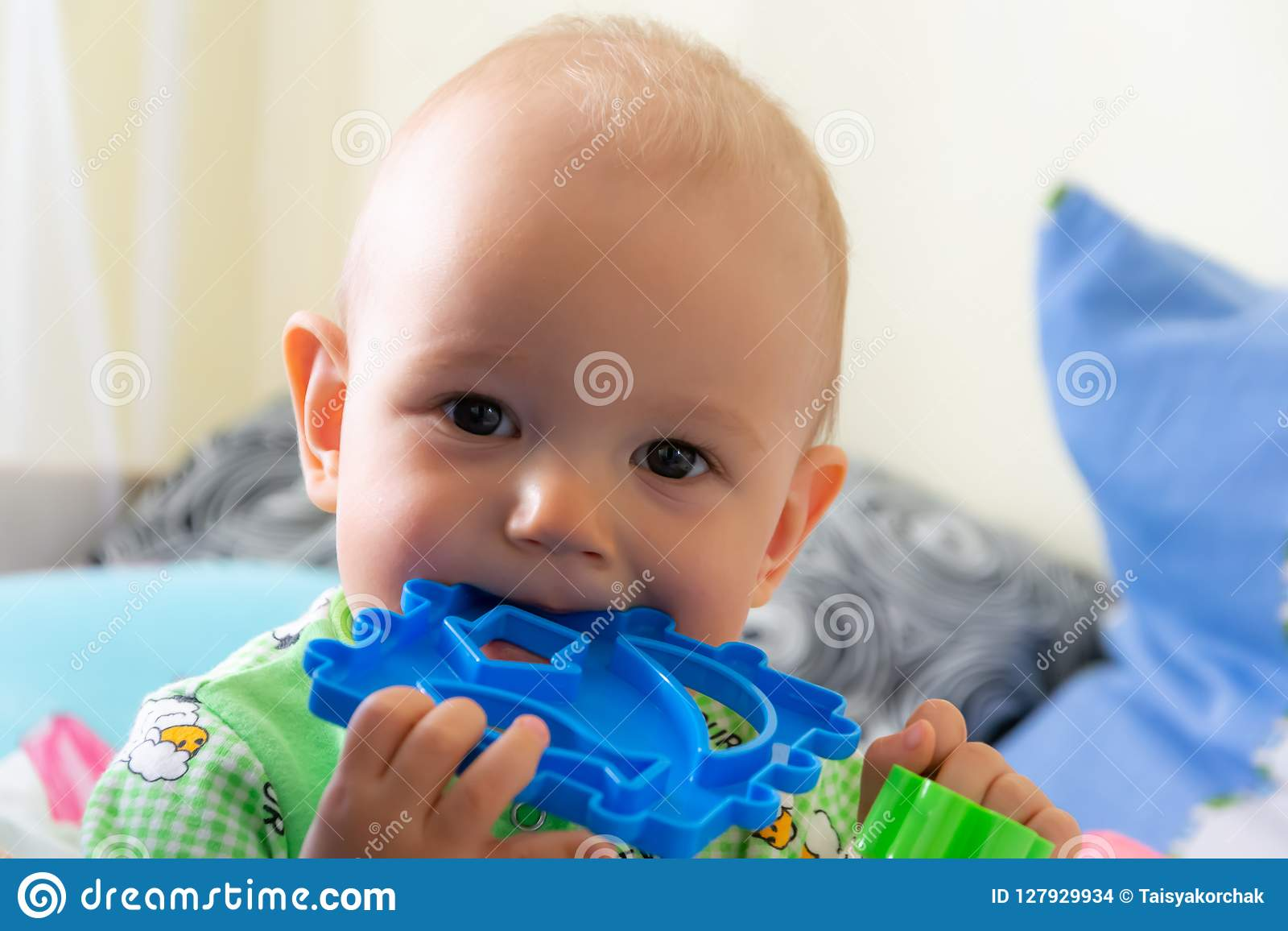 El bebé de un año roe un juguete plástico porque su dentición Pequeño muchacho alegre en un traje verde claro con las ovejas