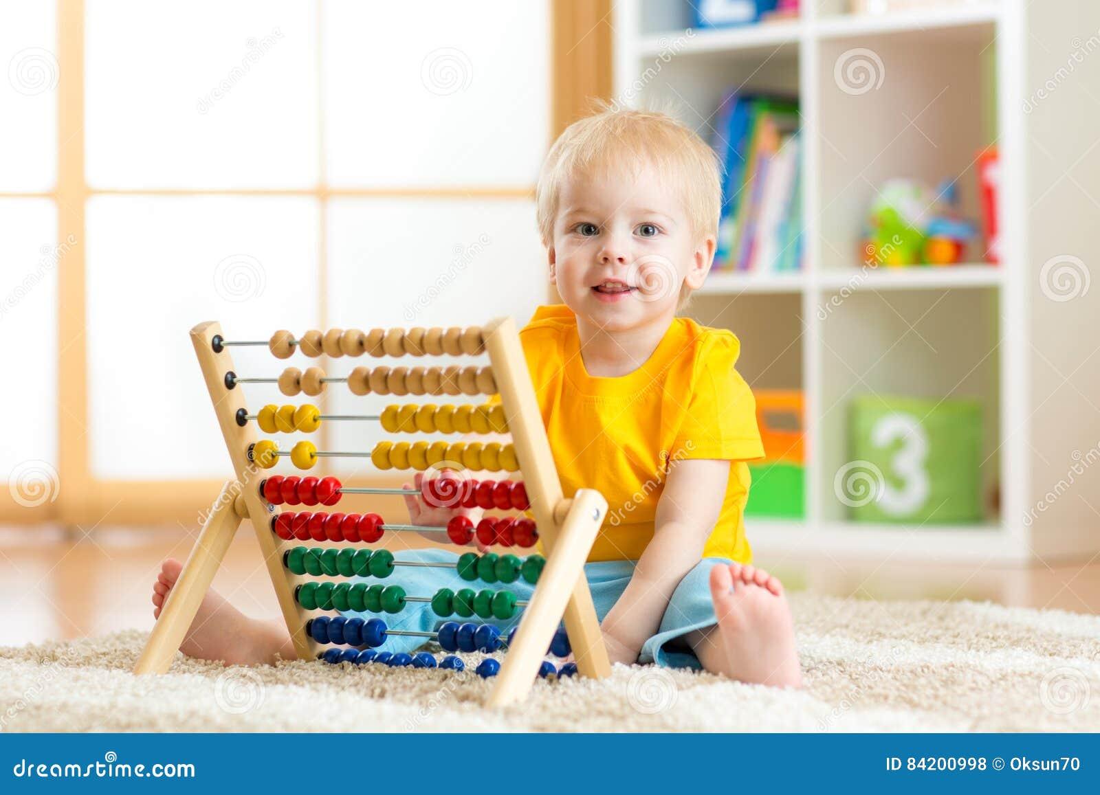 El bebé del preescolar aprende contar Niño lindo que juega con el juguete del ábaco Niño pequeño que se divierte dentro en la gua