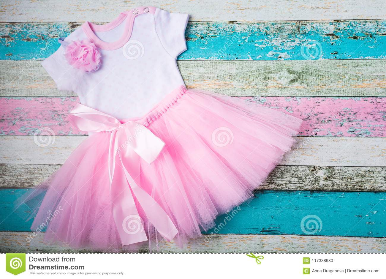 El bebé fijó - la falda rosada de Tulle, el mono blanco de corazones y una venda rosada hermosa sobre fondo de madera en colores