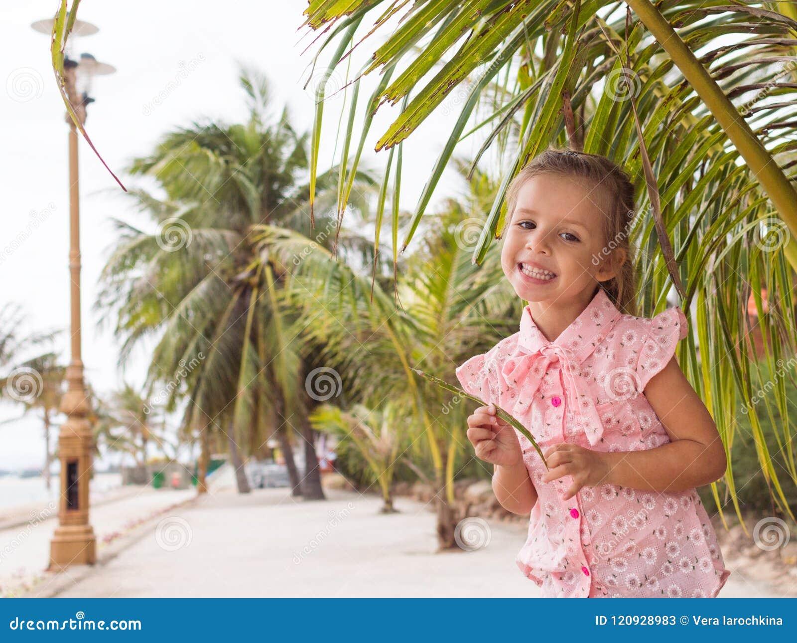 El bebé hermoso en la camisa rosada está permaneciendo cerca de la palma y de la sonrisa