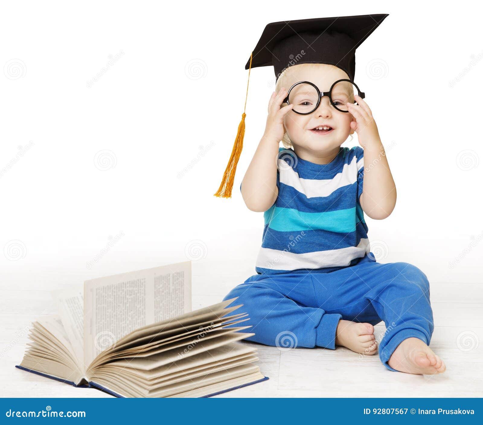 El bebé leyó el libro, el muchacho elegante del niño en vidrios y el sombrero del birrete