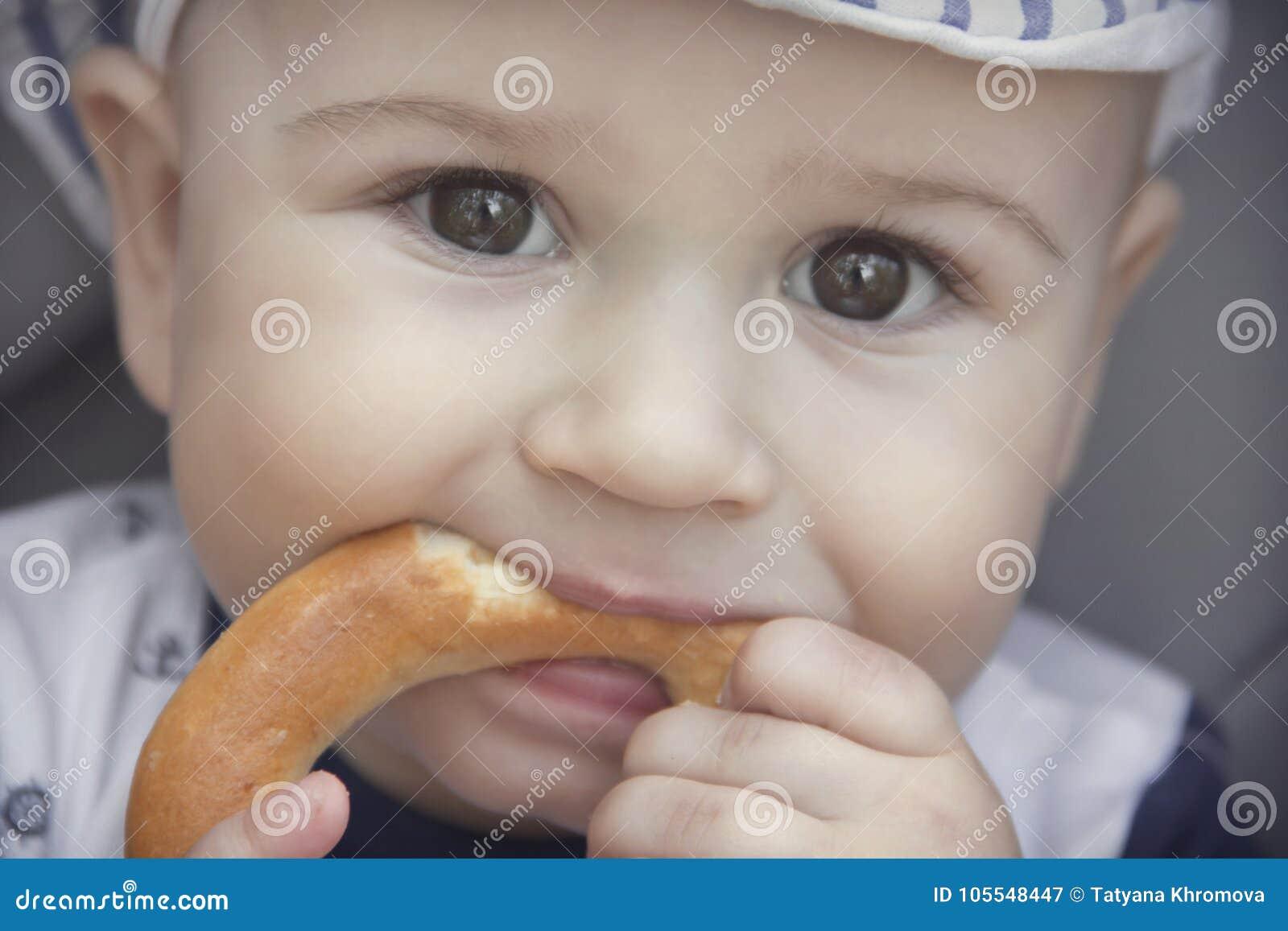 El bebé lindo con un apetito está comiendo un panecillo