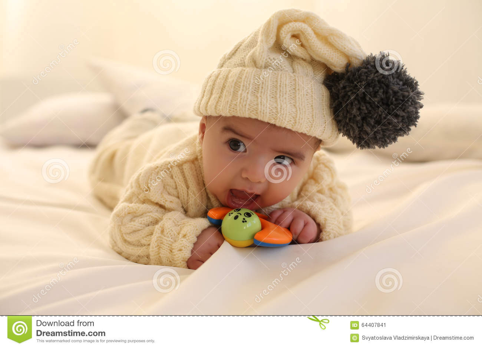 El bebé lindo, lleva la ropa hecha punto, divirtiéndose en el hogar acogedor